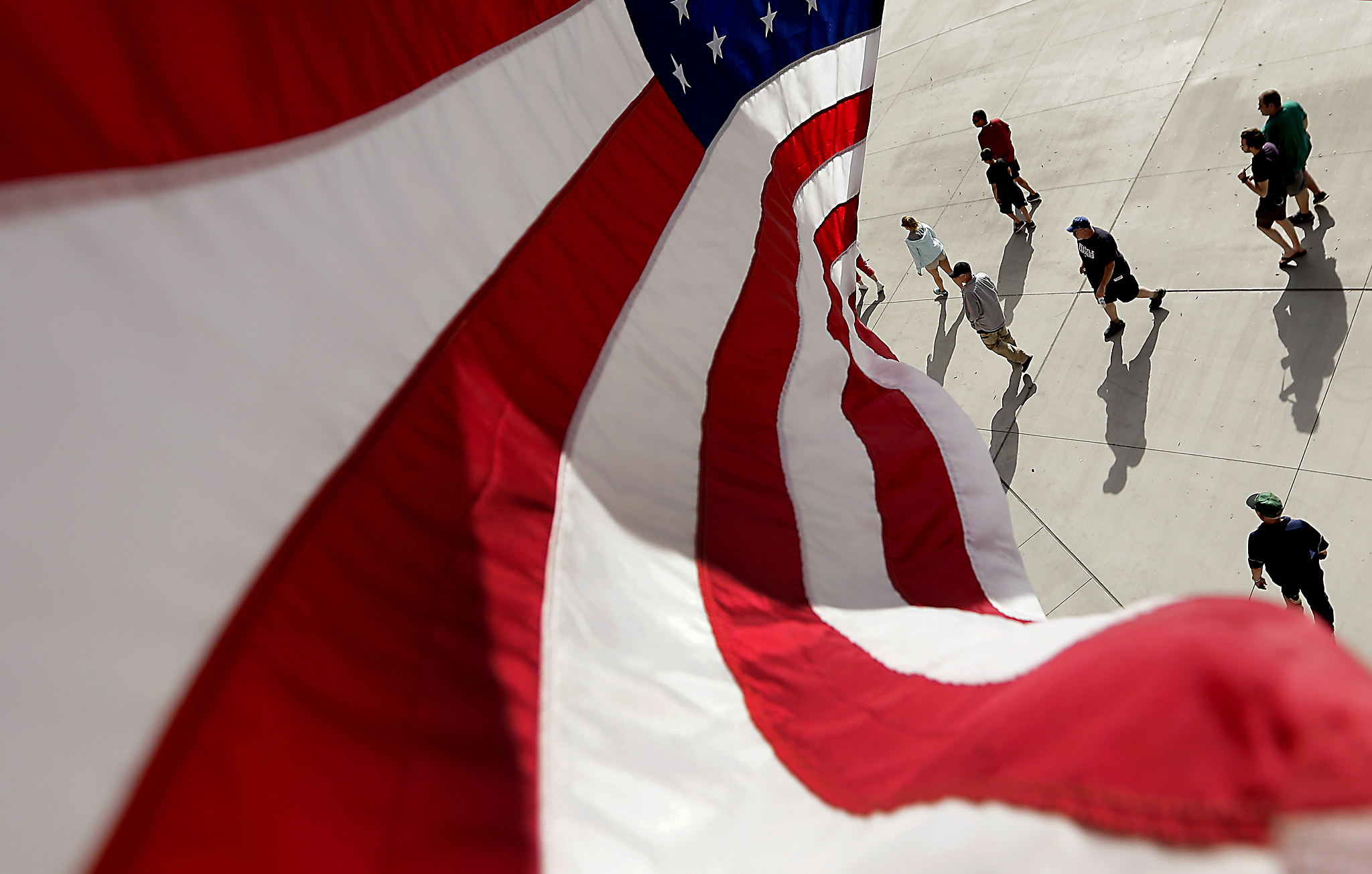 Diamondbacks Mariners Spring Baseball...Fans walk through a concourse under a United States flag during the seventh inning of a spring training baseball game between the Seattle Mariners and the Arizona Diamondbacks, Monday, March 7, 2016, in Peoria, Ariz. (AP Photo/Charlie Riedel)