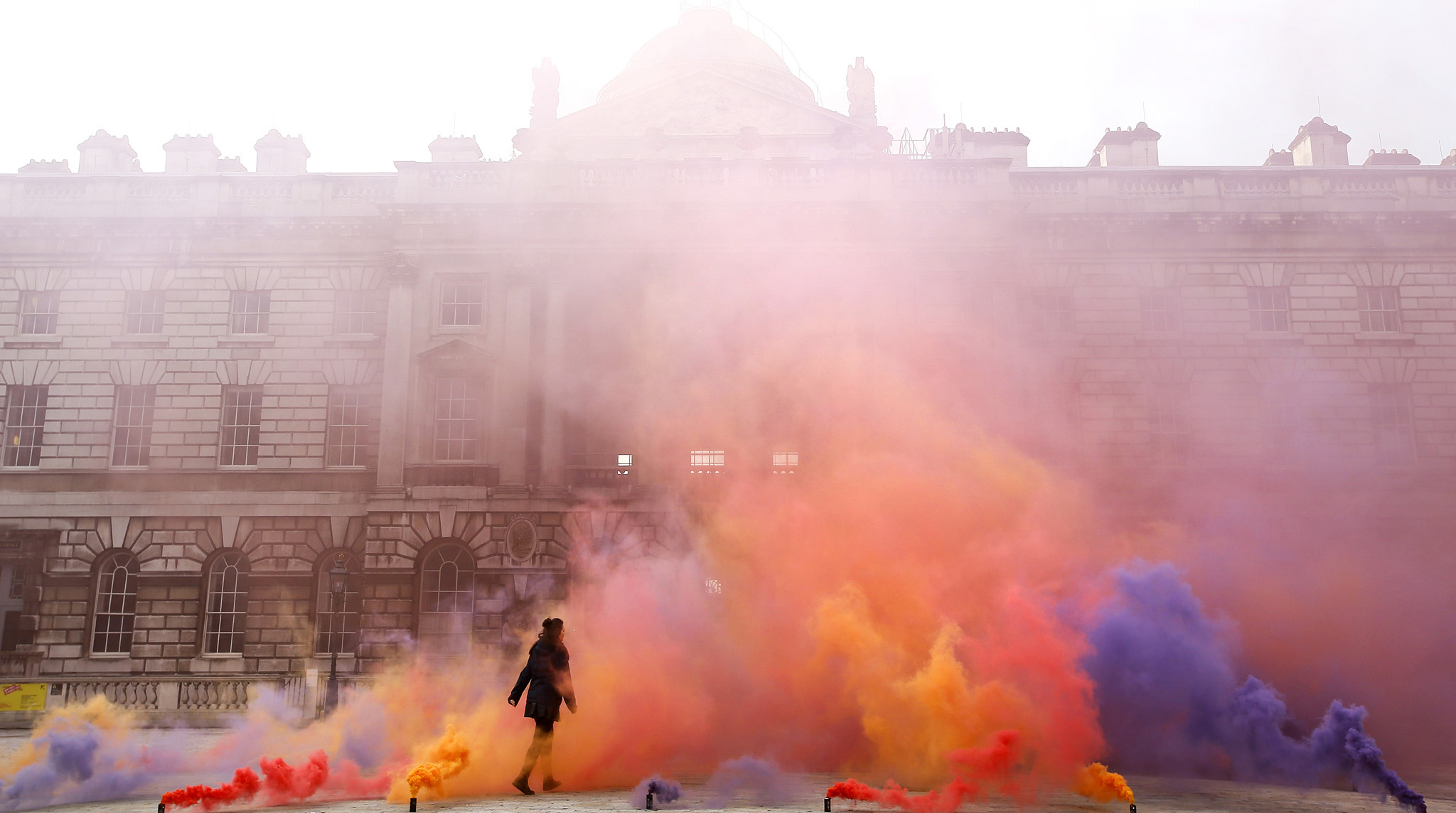 A woman walks through artwork created by artist Filippo Minelli in his series Silence / Shapes in Somerset House
