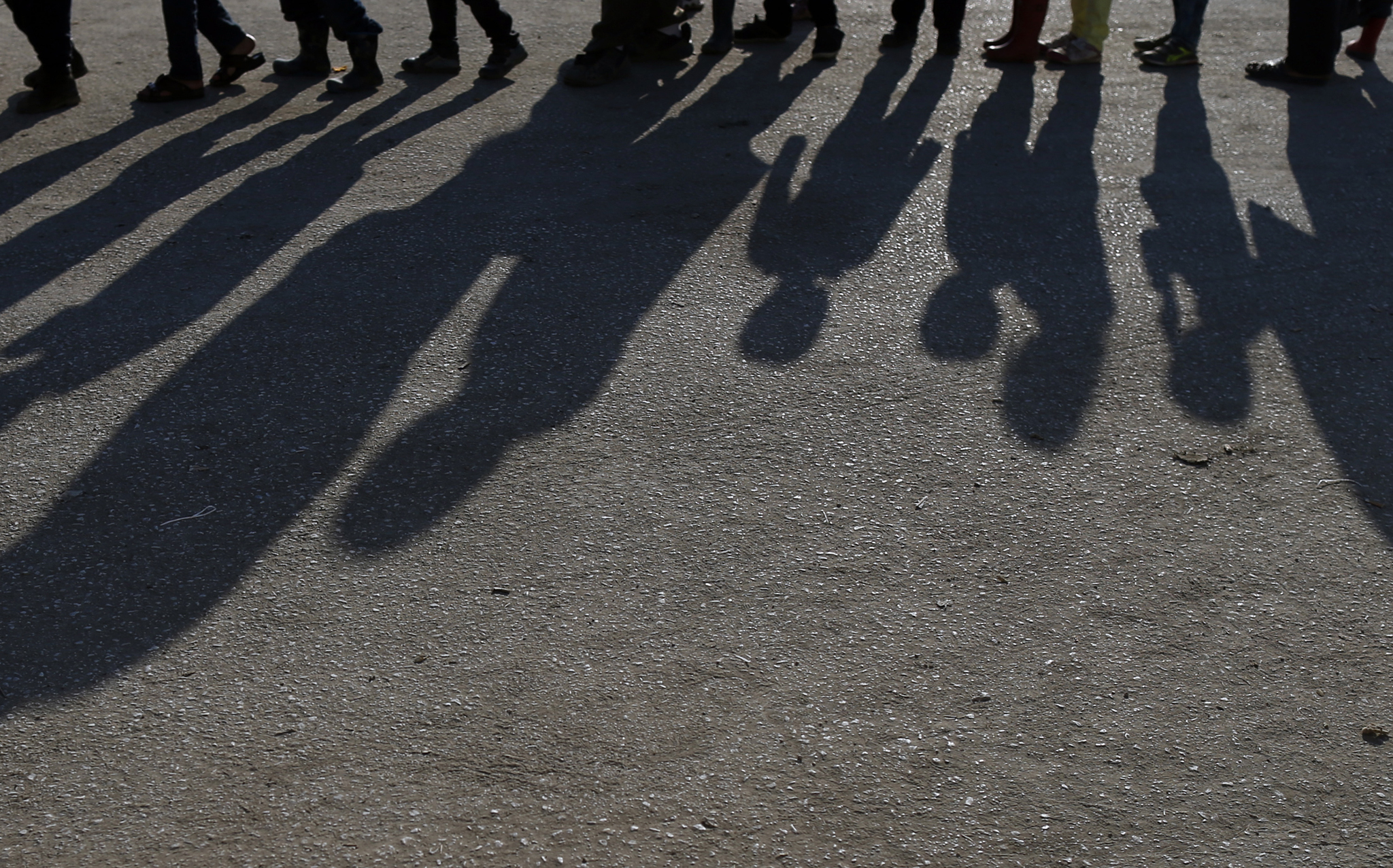 A shadow of migrants wait for food in the makeshift refugee camp at the northern Greek border point of Idomeni, Greece