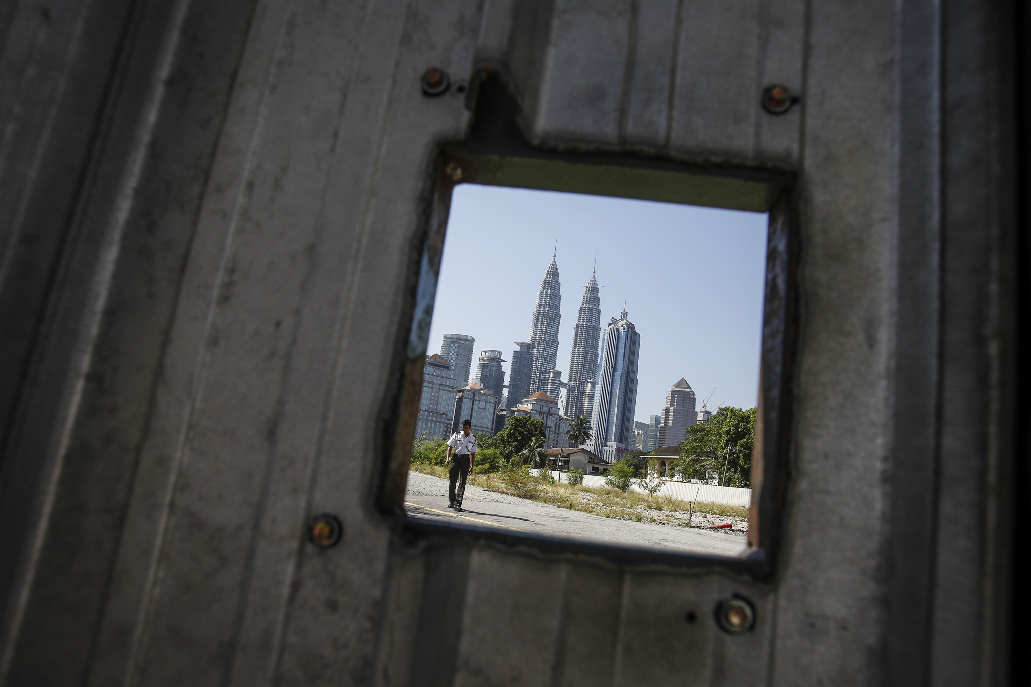 A security guard patrols at a construction site in front of Petronas Twin Tower