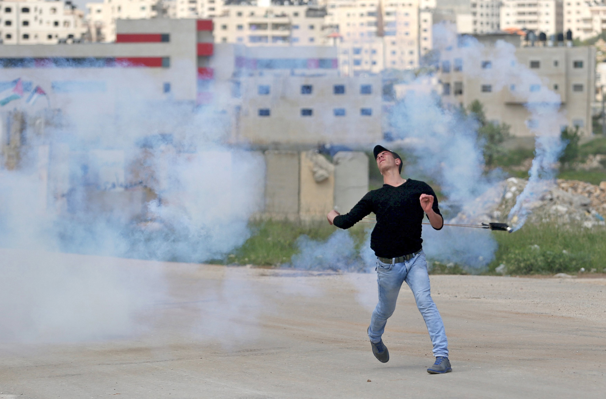 A Palestinian protester uses a sling to return a tear gas canister fired by Israeli troops during clashes at a protest marking Land Day, near Israel's Ofer Prison near the West Bank city of Ramallah March 30, 2016. March 30 marks Land Day, the annual commemoration of protests in 1976 against Israel's appropriation of Arab-owned land in the Galilee
