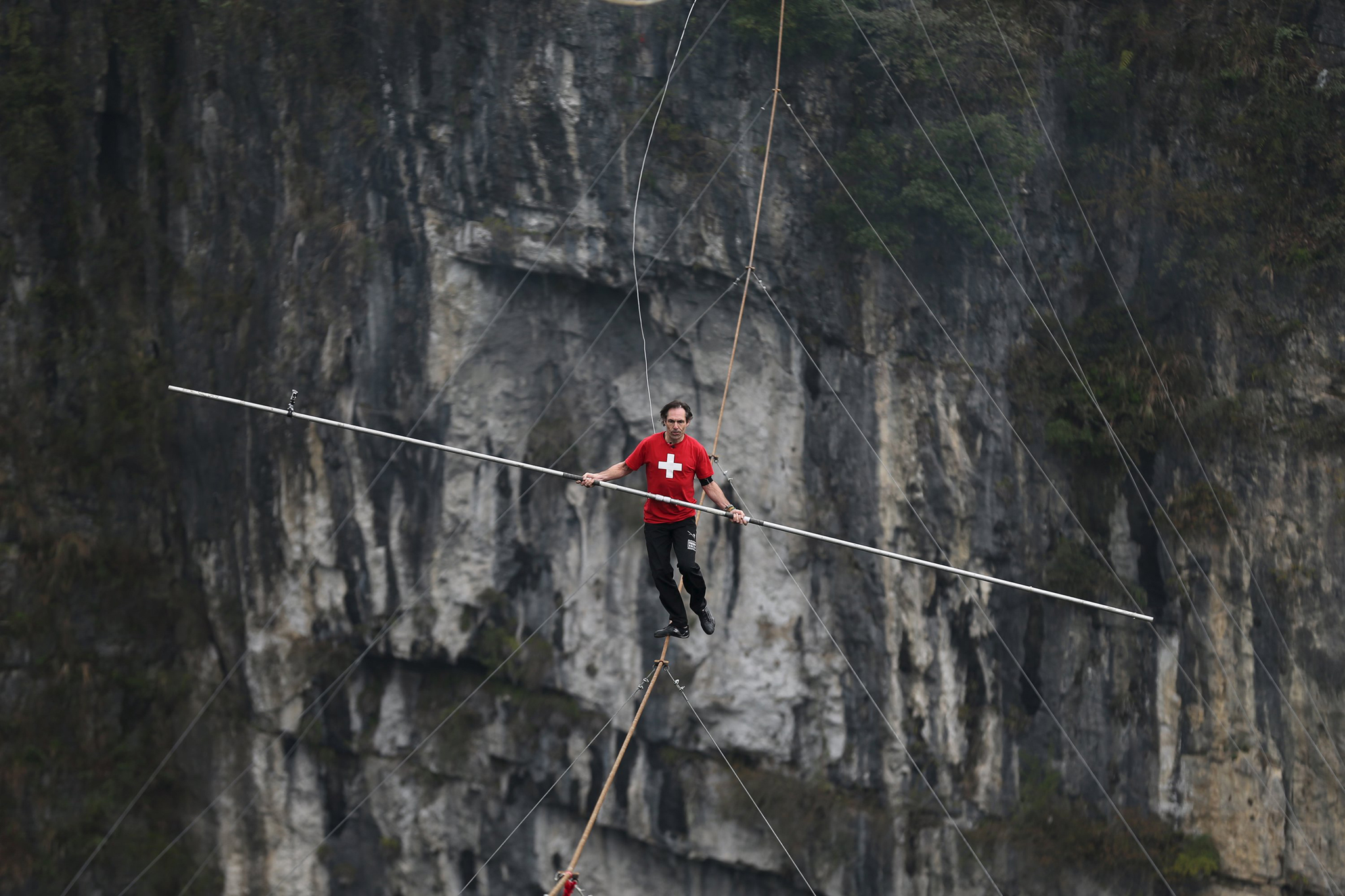 Freddy Nock of Switzerland walks on tightrope during a competition in Wulong county, Chongqing, China, March 30, 2016.