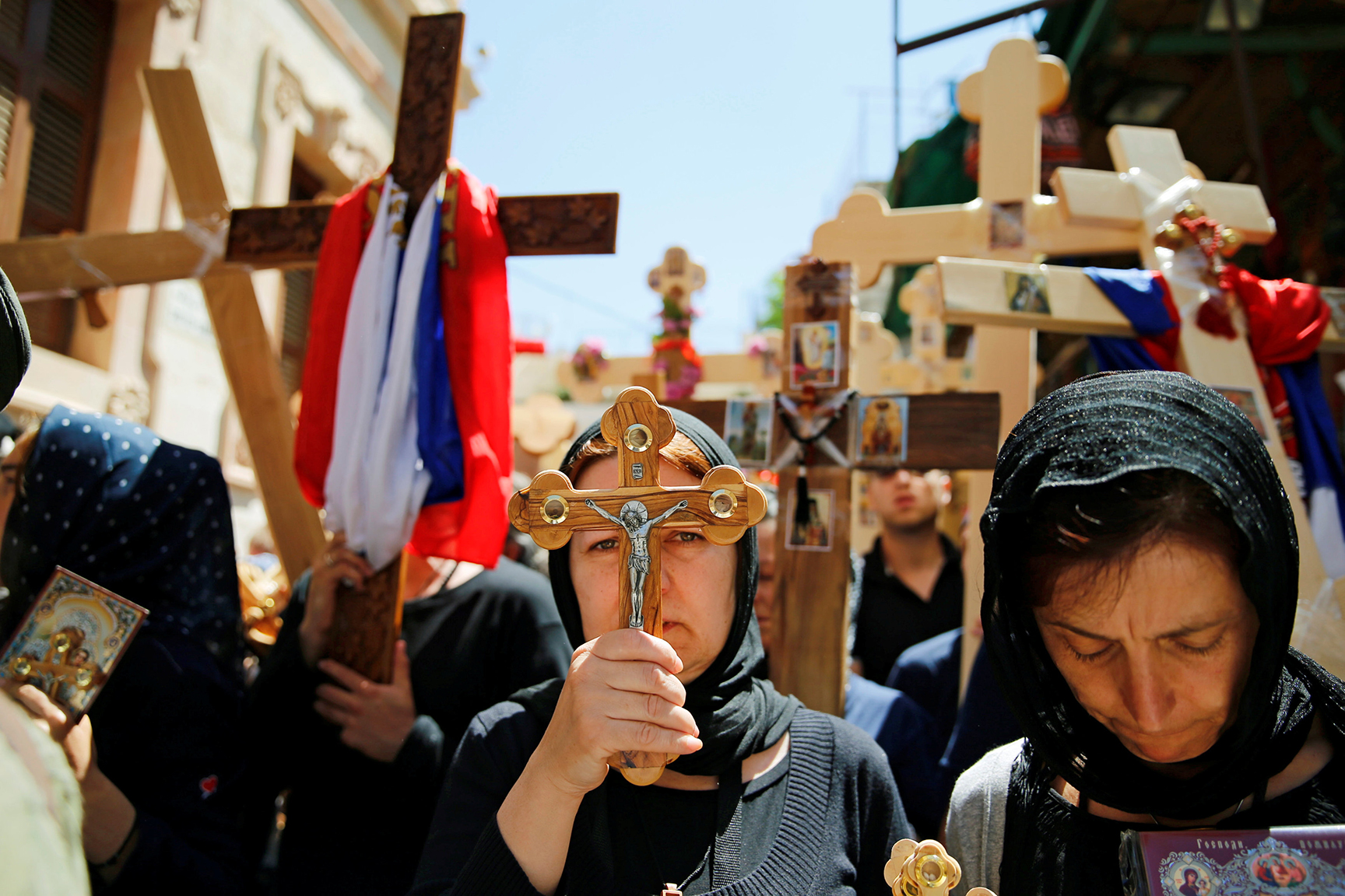 Orthodox Christian worshippers hold crosses before a procession along the Via Dolorosa on Good Friday during Holy Week in Jerusalem's Old City