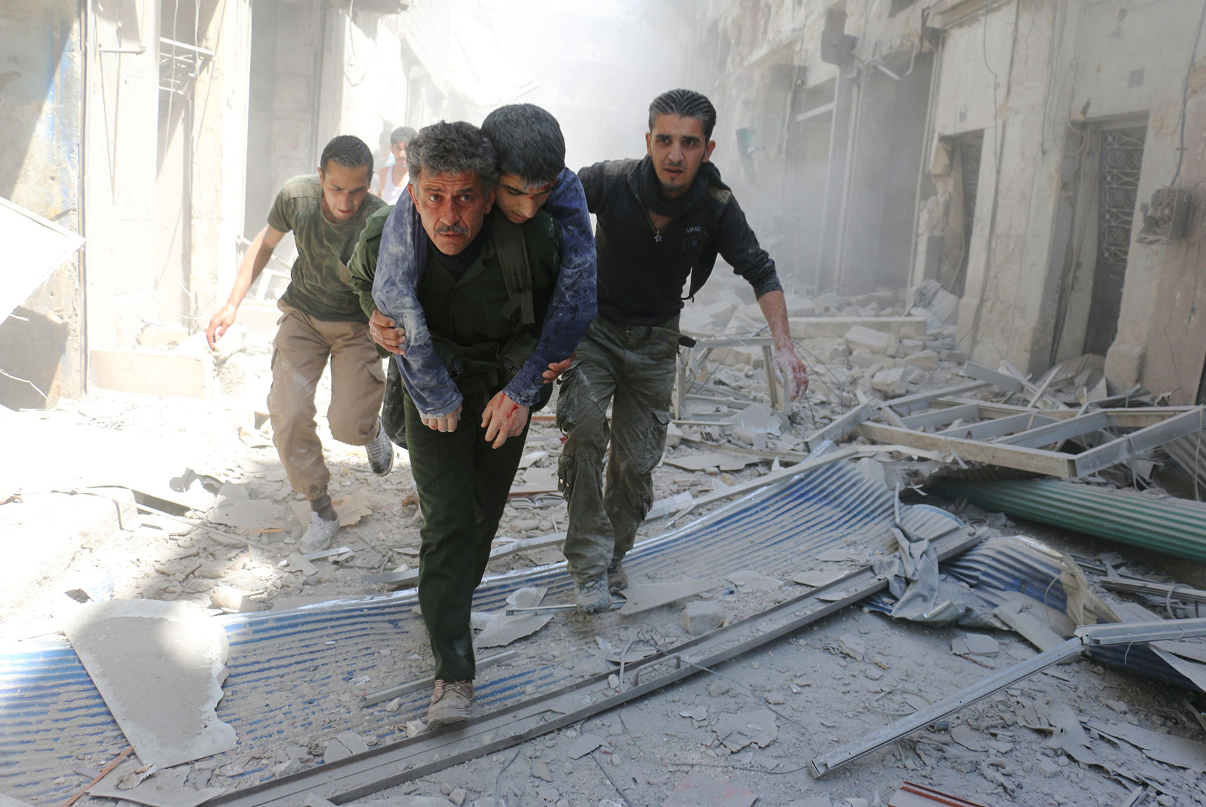 Syrians evacuate an injured man