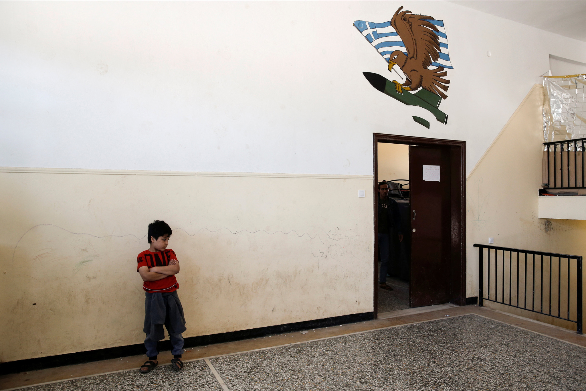 A boy stands inside a building used as sleeping quarters at camp for refugees and migrants in Schisto, near Athens...A boy stands inside a building used as sleeping quarters at camp for refugees and migrants in Schisto, near Athens, Greece, April 26, 2016. REUTERS/Alkis Konstantinidis GREECE OUT. NO COMMERCIAL OR EDITORIAL SALES IN GREECE