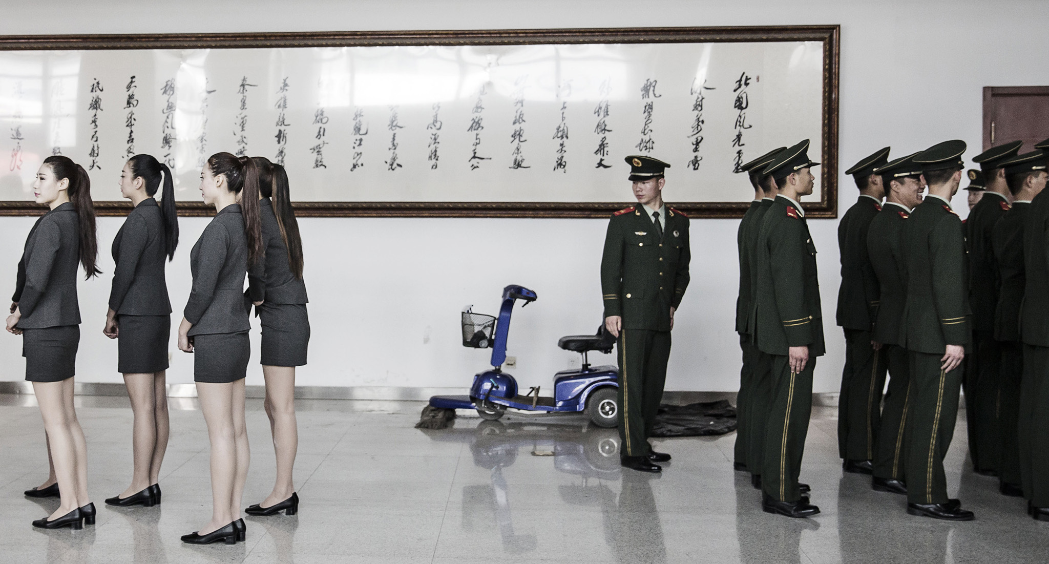 Inside The Beijing International Automotive Exhibition...A paramilitary police officer (right) turns around as hostesses line up for roll call ahead of the Beijing International Automotive Exhibition in Beijing, China, on Monday, April 25, 2016. Tesla Motors Inc. and BYD Co. are among manufacturers showing 147 new-energy vehicles at this year's show.