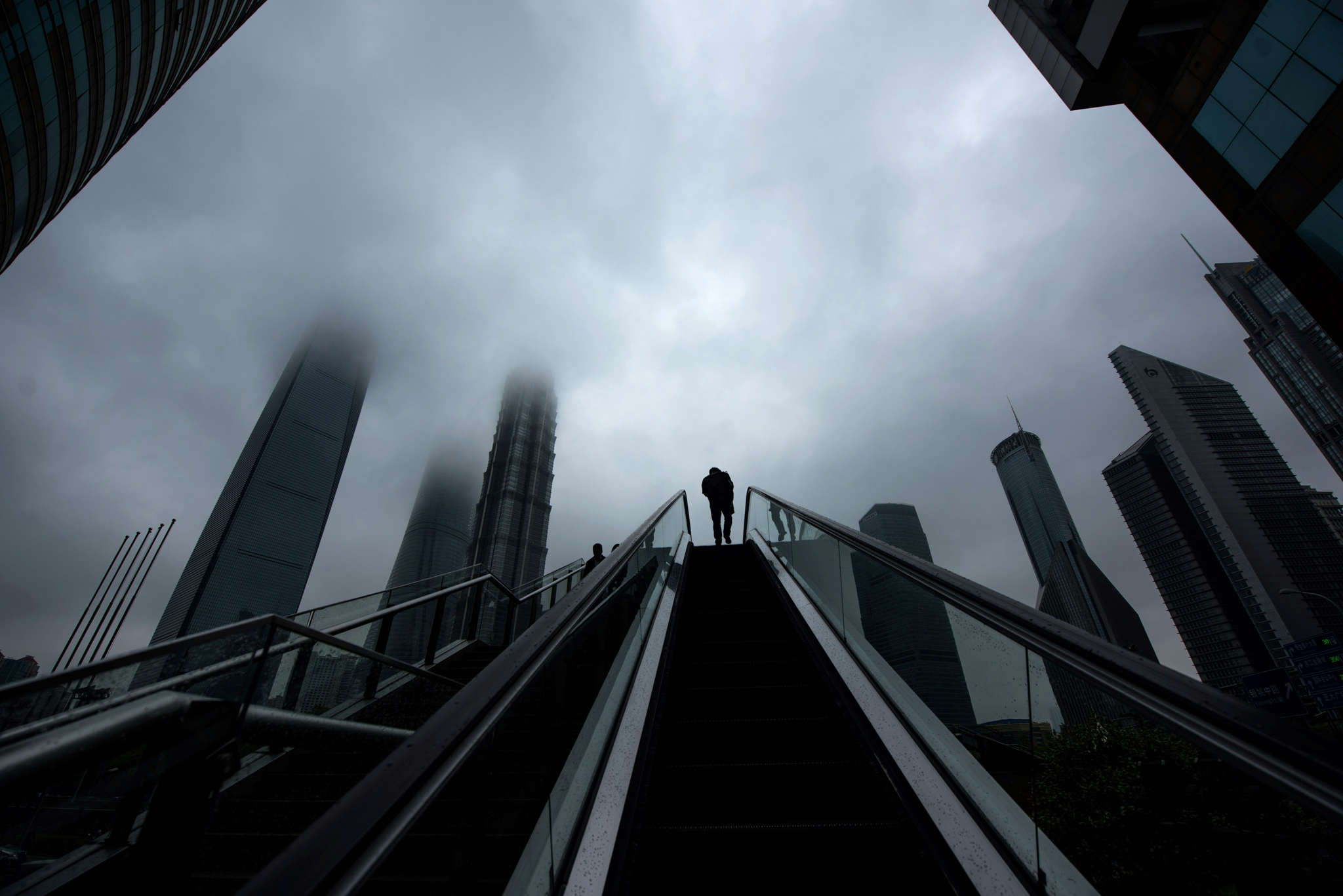 A man rides an escalator in front of hig...A man rides an escalator in front of high rise buildings in the financial district Lujiazui in Shanghai on April 6, 2016.  / AFP PHOTO / JOHANNES EISELEJOHANNES EISELE/AFP/Getty Images