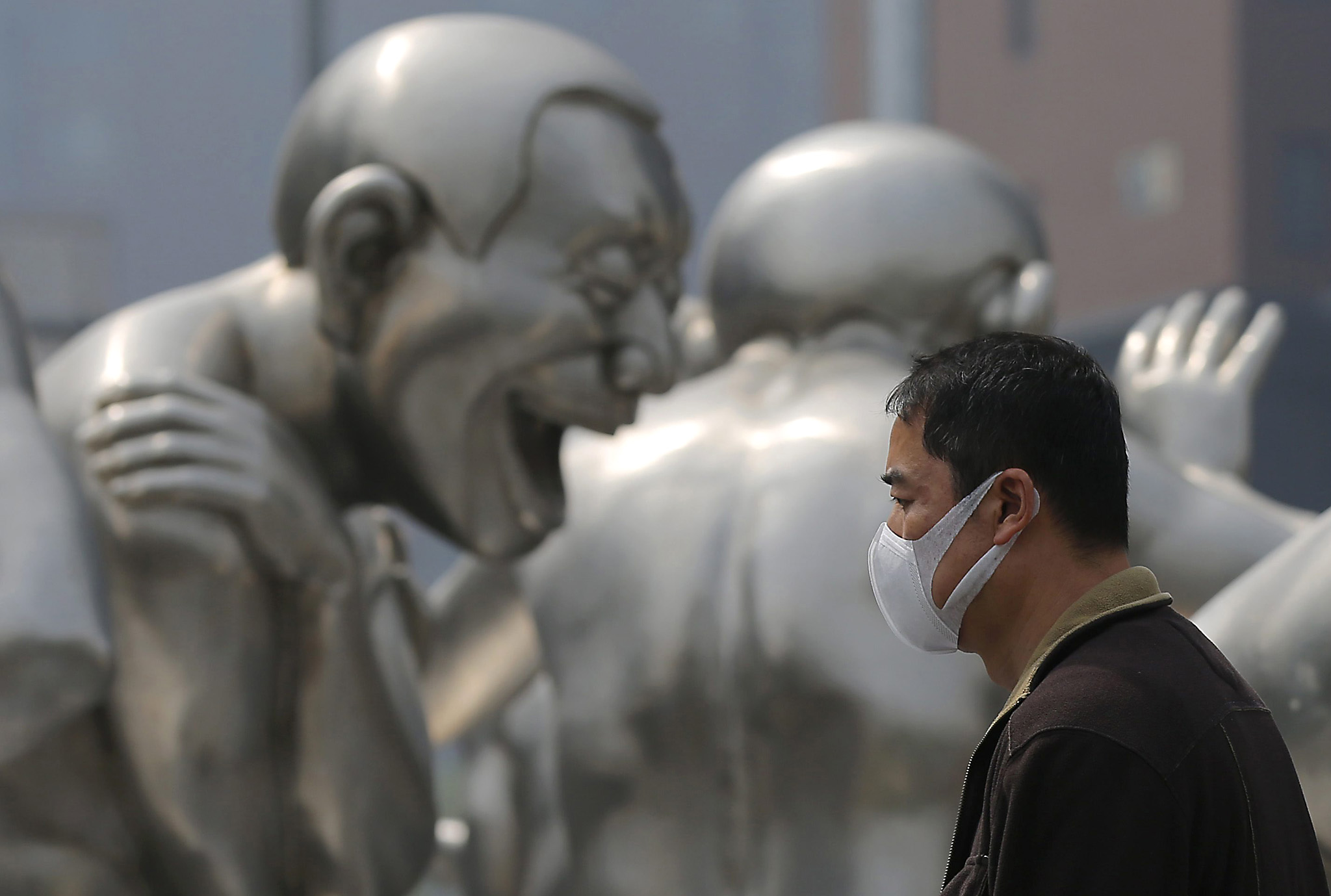 Air pollution in Beijing...epaselect epa05256265 A Chinese, wearing a mask, passes by a sculpture during a smoggy day in Beijing city, China, 13 April 2016. The Chinese Ministry of Environmental Protection received about 15,000 public complaints about pollution in 2015. The air pollution tip-offs became the top 78.3 percent of all complaints received through the ministry's hotline and 68 percent through the WeChat, according to the media reports.  EPA/WU HONG