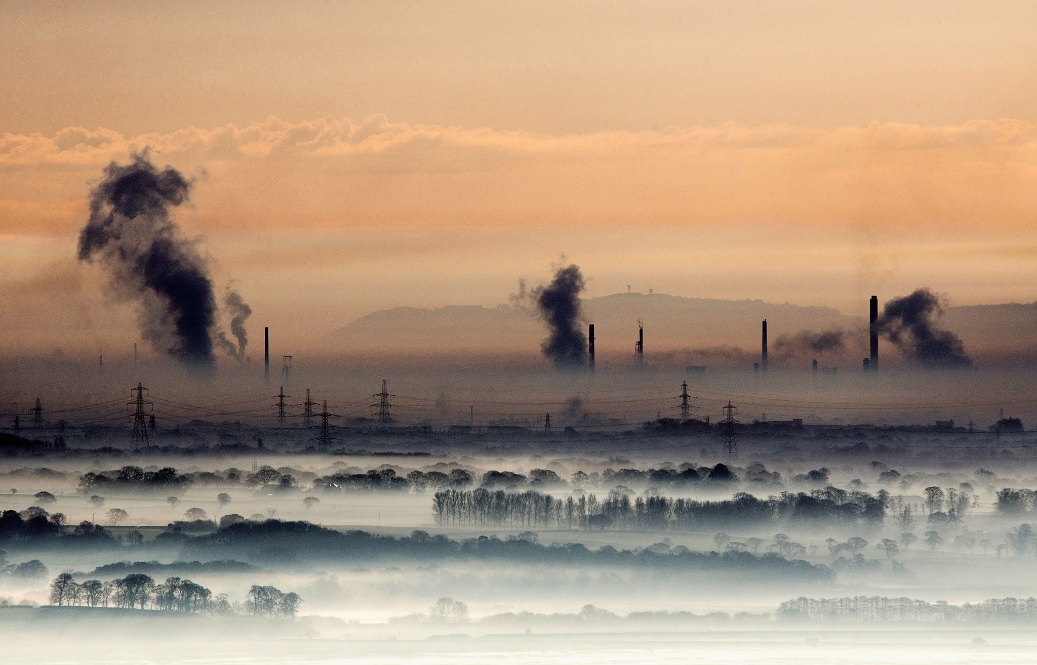 Industrial Views Across The Dee Valley...FLINT, WALES - APRIL 13:  The industrial landscape across the Dee Estuary at sunrise as steam rises from Deeside power station, Shotton Steelworks and other heavy industrial plants on April 13, 2016 in Flint, Wales. The British Steel industry has been plunged into crisis after Tata Steel announced it would begin the process of selling its loss-making plants in the UK, putting thousands of jobs at risk.