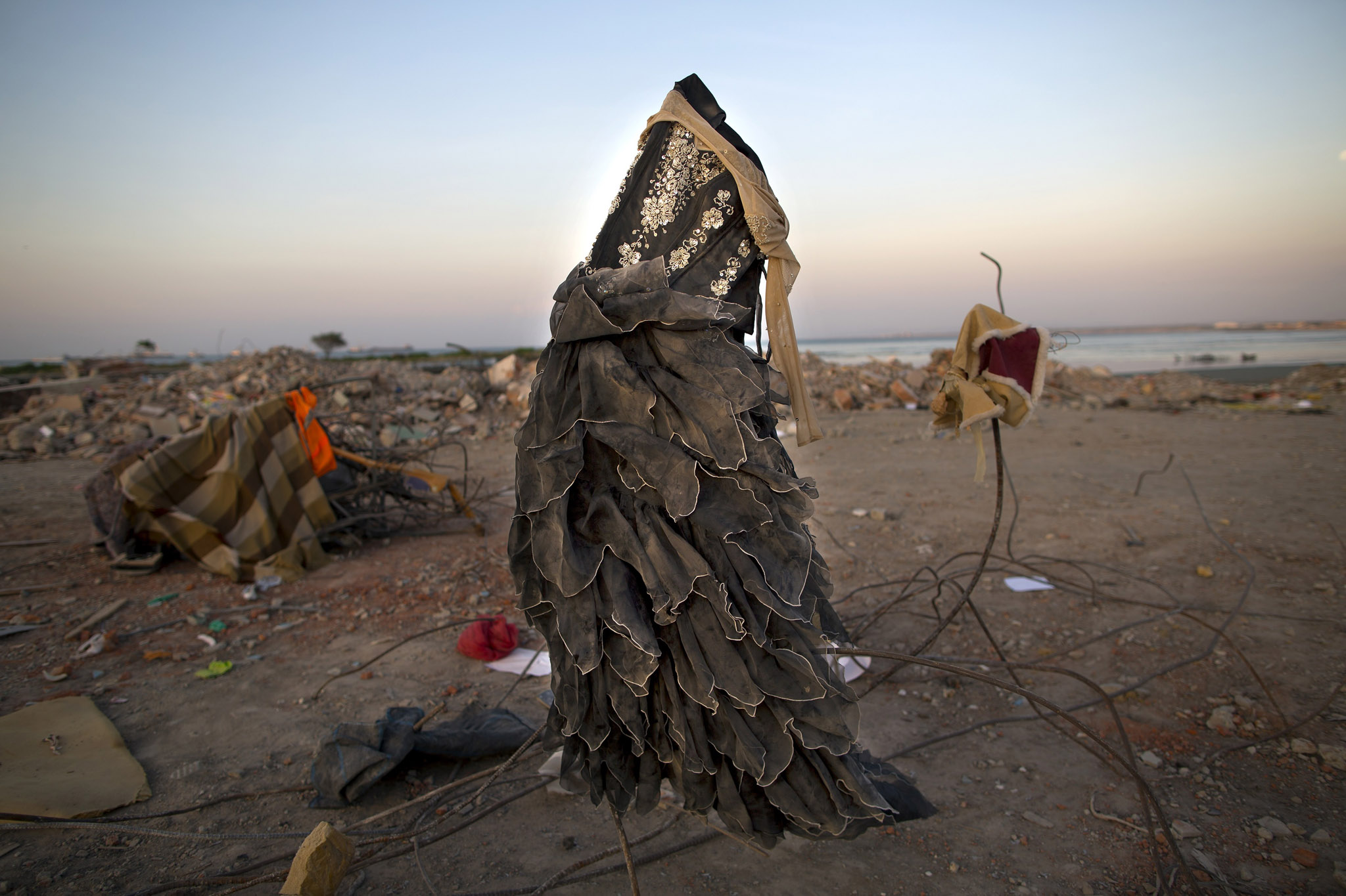 A dress hangs from twisted metal as residents comb through a post-earthquake debris field, salvaging recyclable material, in Manta, Ecuador, Wednesday, April 20, 2016. Ecuadoreans began burying loved ones felled by the country's deadliest earthquake in decades, while hopes faded that more survivors will be found. (AP Photo/Rodrigo Abd)