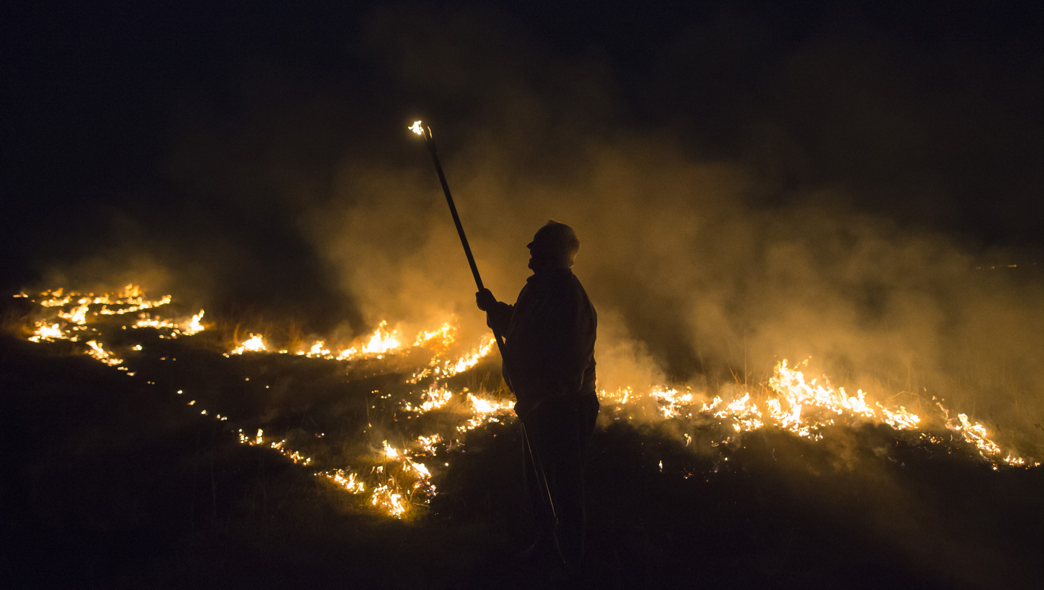 Rancher Fred Berns holds fire pole while lighting a controlled pasture fire near Florence, Kan., Wednesday, April 13, 2016. Ranchers in the Flint Hills of Kansas routinely burn their pastures in the spring to promote the growth of new grass for cattle to graze on. (Travis Heying/The Wichita Eagle via AP) LOCAL TELEVISION OUT; MAGS OUT; LOCAL RADIO OUT; LOCAL INTERNET OUT; MANDATORY CREDIT