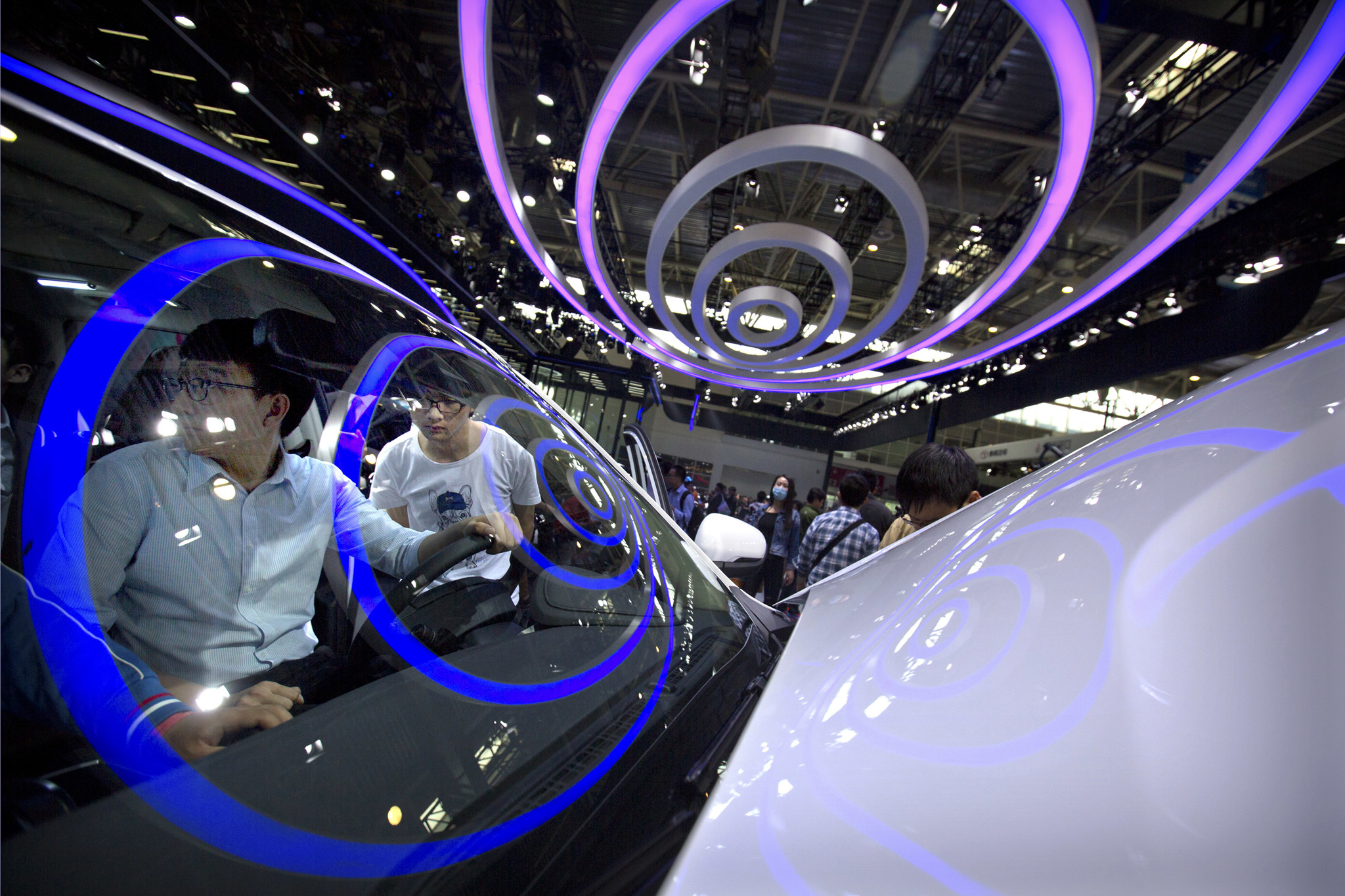 Visitors look at a Boyue SUV by Chinese automaker Geely at the Beijing International Automotive Exhibition in Beijing, Wednesday, April 27, 2016. The auto show, which opened to the public on Wednesday, continues through May 4. (AP Photo/Mark Schiefelbein)