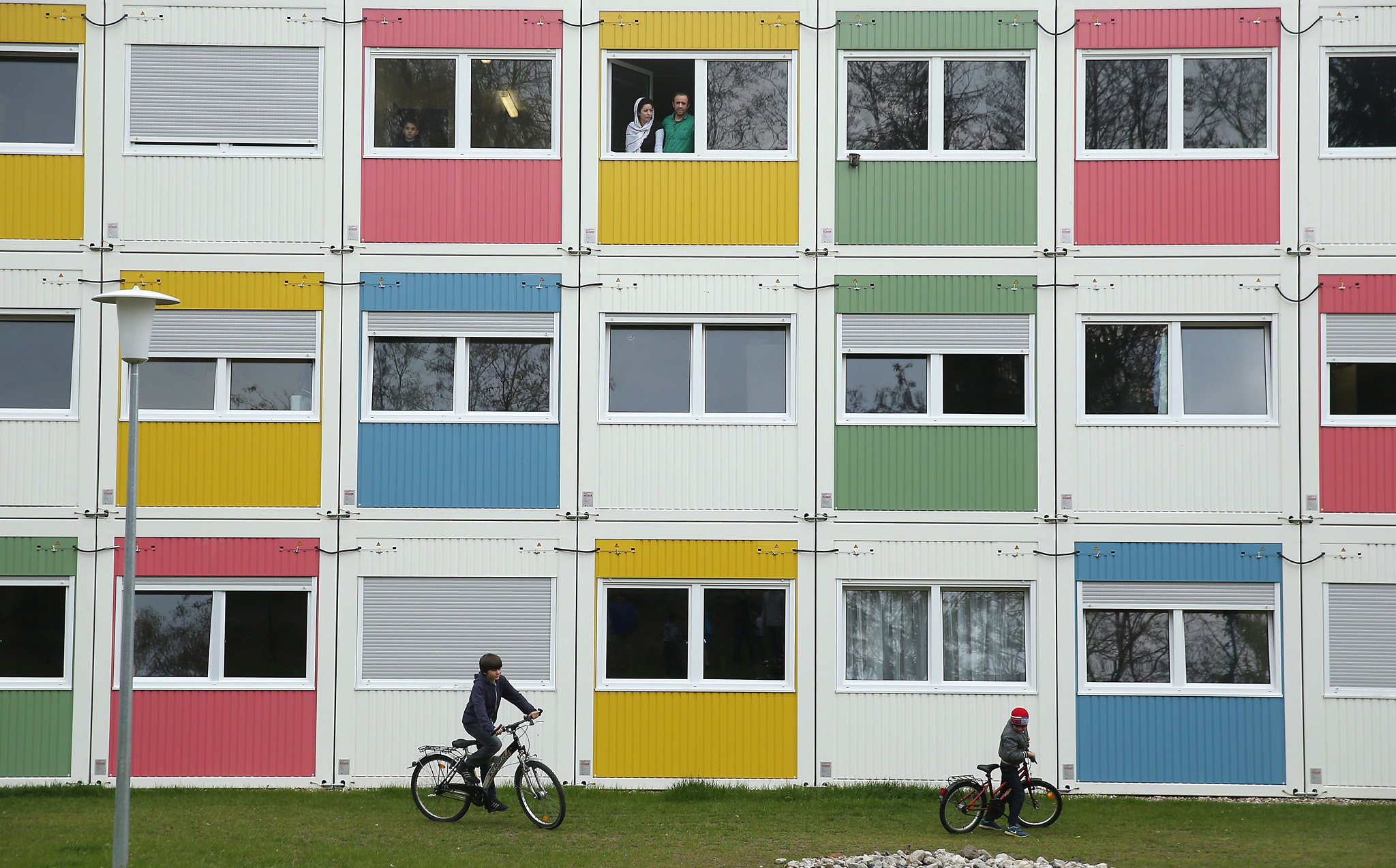 As Refugee Flow Ebbs Germany Concentrates On Integration...BERLIN, GERMANY - APRIL 14:  Children play as residents look from their window at the container settlement shelter for refugees and migrants in Zehlendorf district on April 14, 2016 in Berlin, Germany. Locals, many of them retirees, come to the shelter regularly to help the refugees and migrants, who are from countries including Syria, Iraq, Afghanistan, Kosovo and Serbia. The coalition partners of the German government yesterday announced a new package of legislation that includes measures to foster the integration of refugees who have received asylum status in Germany.  (Photo by Sean Gallup/Getty Images)