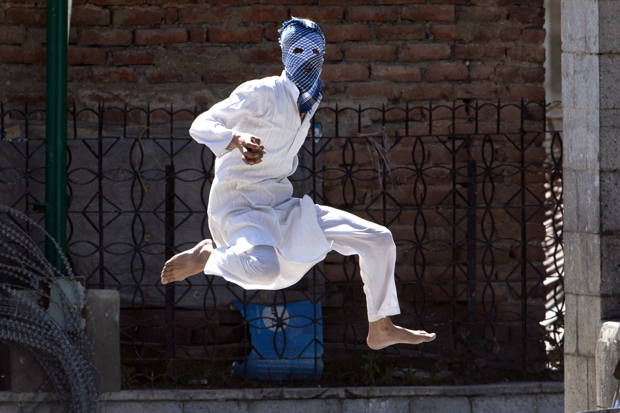 A Kashmiri masked Muslim protester jumps in the air to avoid stones thrown at him by Indian police during a protest in Srinagar, Indian controlled Kashmi
