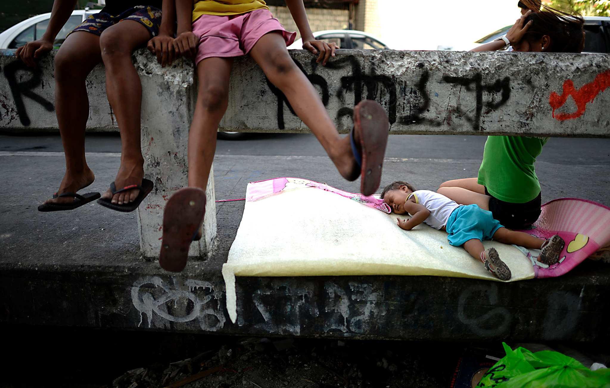 TOPSHOT - A child sleeps on a bridge in ...TOPSHOT - A child sleeps on a bridge in Manila on April 6, 2016.  Roughly one quarter of the nation's 100 million people live in poverty, which is defined as surviving on about one US dollar a day, according to government data / AFP PHOTO / NOEL CELISNOEL CELIS/AFP/Getty Images