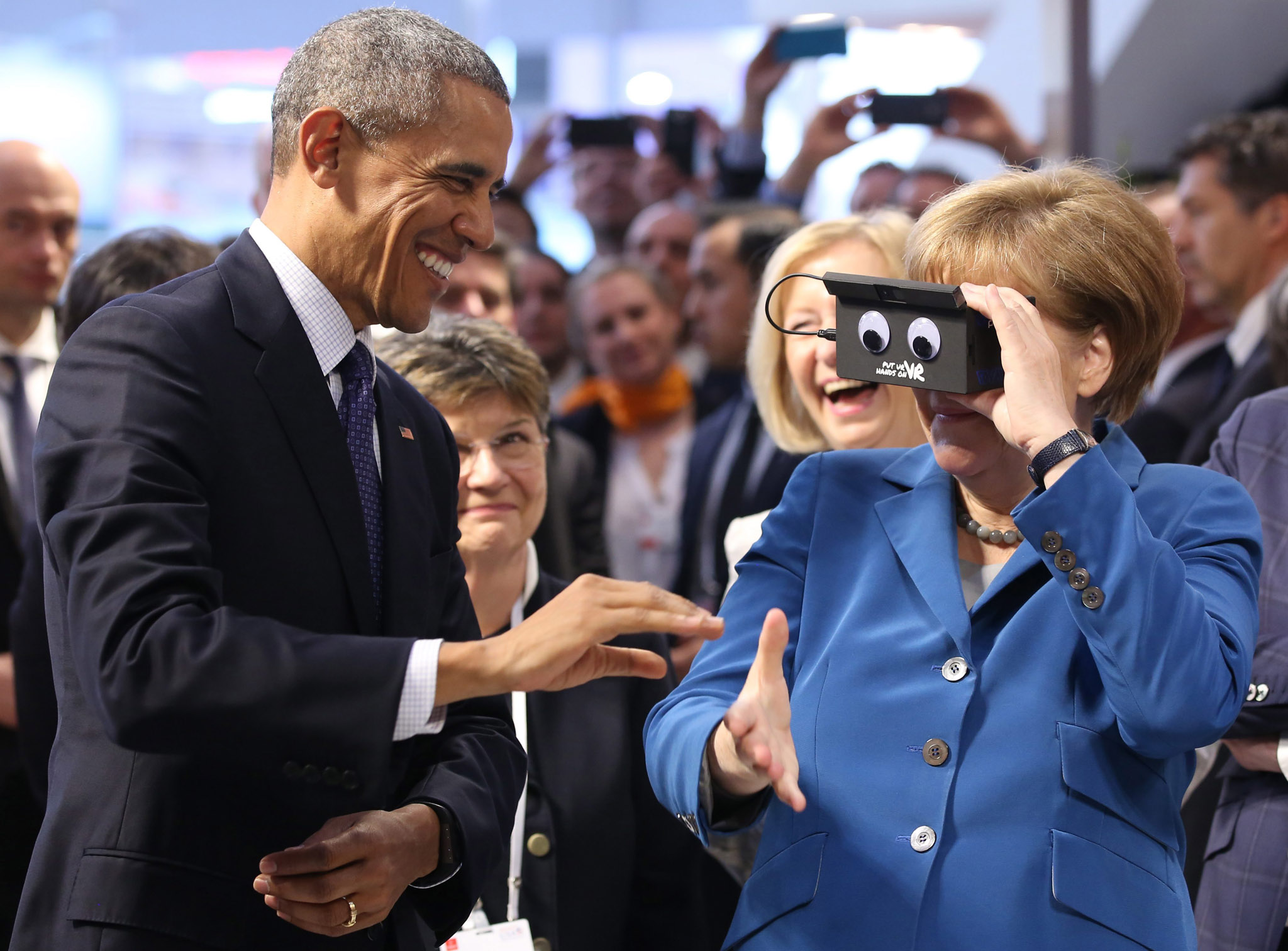 US President Barack Obama visits Germany...epa05276425 German†Chancellor Angela Merkel (R) tests a Virtual Reality (VR) goggle next to US†President Barack Obama (L) as they visit the booth of ifm electronic (automation engineering) at the Hannover Messe industrial technology trade fair in Hanover,†Germany, 25 April 2016. The USA is this year's partner country at the trade fair. The US President is on a two-day visit to Germany.  EPA/CHRITSTIAN†CHARISIUS