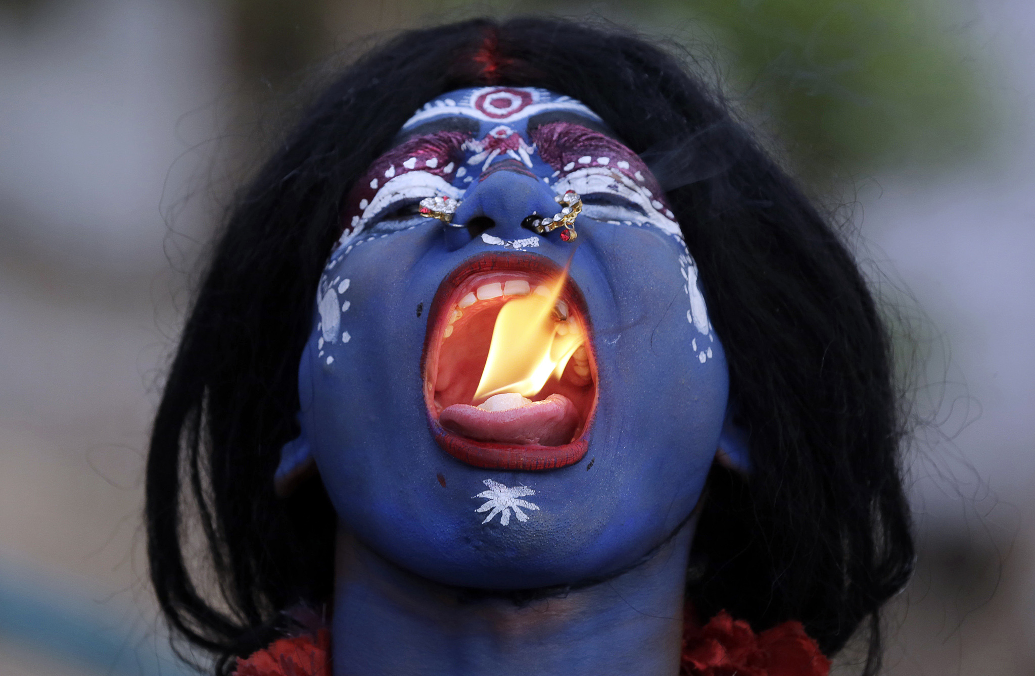 An Indian man dressed as Hindu Goddess Kali puts fire in his mouth during a procession to celebrate the Ram Navami festival in Allahabad, India