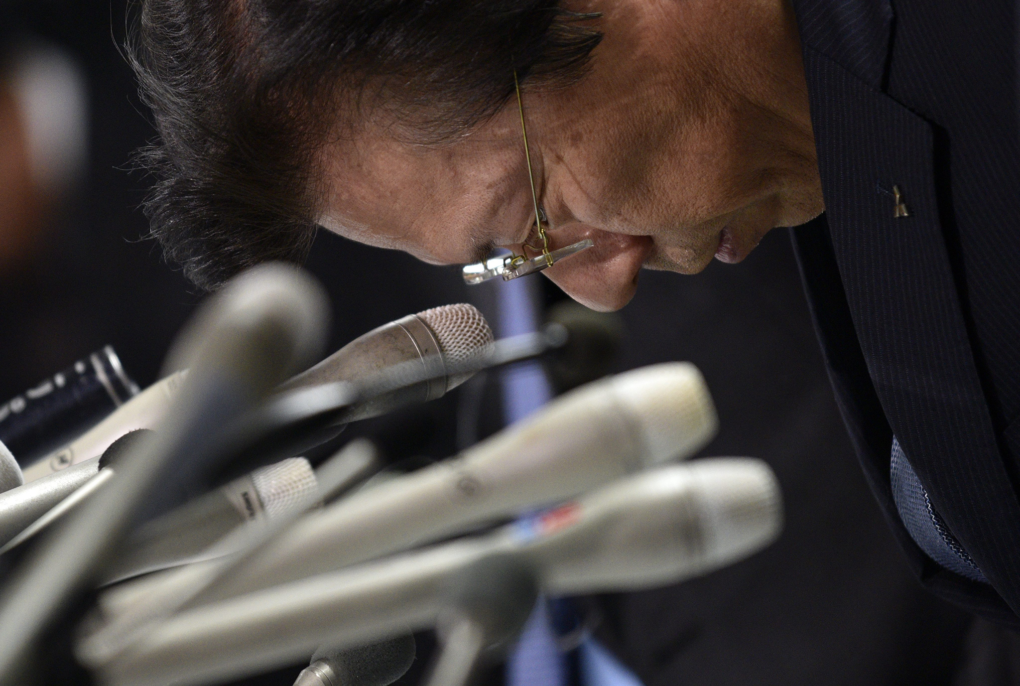 Mitsubishi Motors President Tetsuro Aikawa reacts during a press conference announcing the embattled carmaker's earnings for the fiscal year 2015, in Tokyo