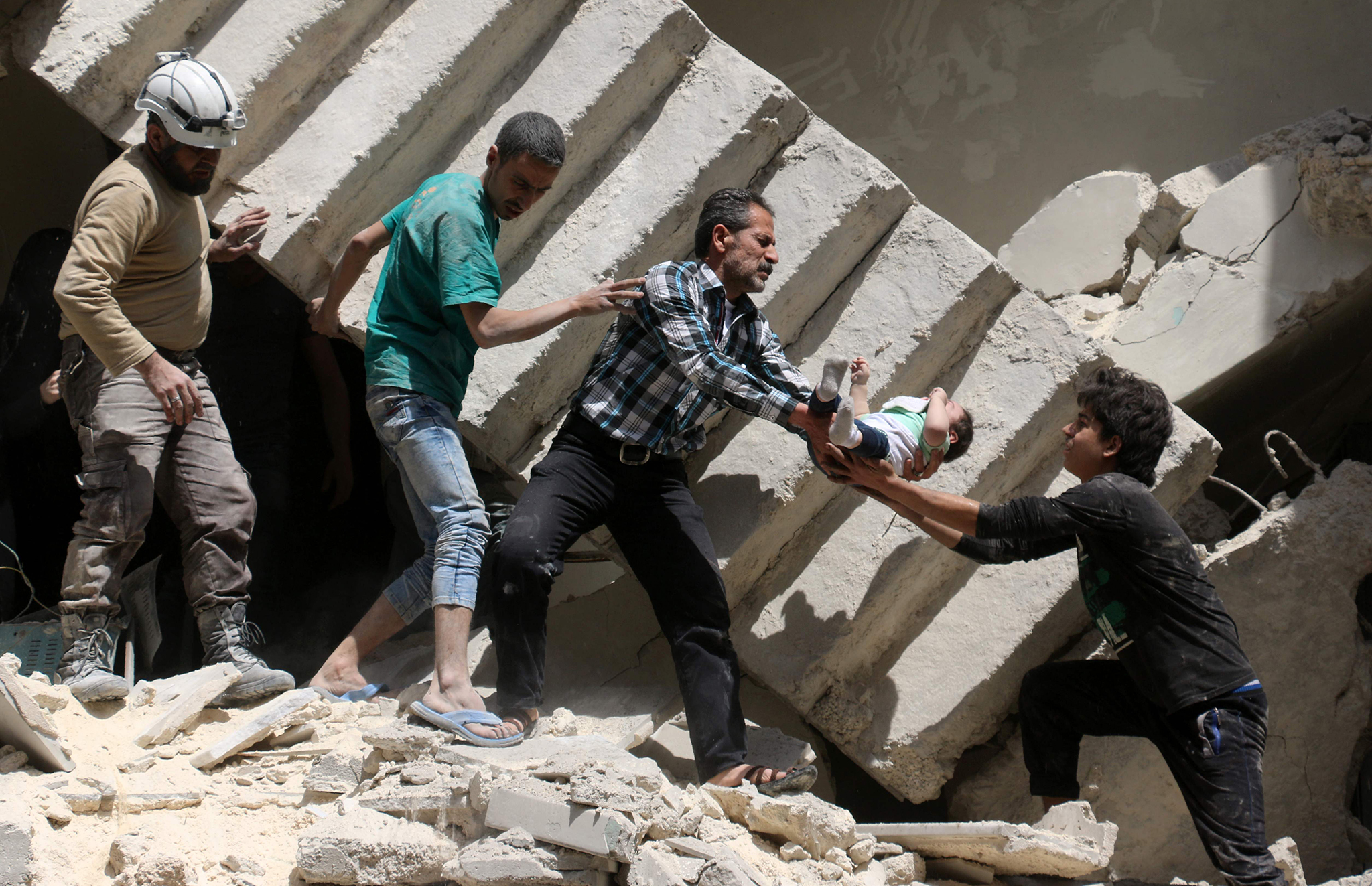Syrian civil defence volunteers and rescuers remove a baby from under the rubble of a destroyed building following a reported air strike on the rebel-held neighbourhood of al-Kalasa in the northern Syrian city of Aleppo.
