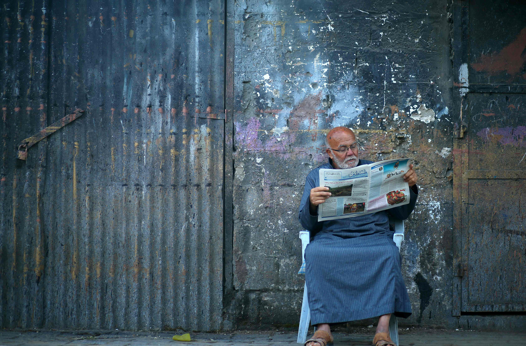 Palestinian man reads a local newspaper outside his home in Gaza City