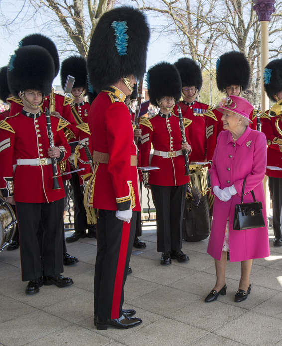 Britain's Queen Elizabeth II , right, talks to a member of the Royal Guard as she officially opens the new Bandstand at Alexandra Gardens, a day ahead of her 90th birthday, in Windsor, England, Wednesday, April 20, 2016. (Arthur Edwards/Pool Photo via AP)