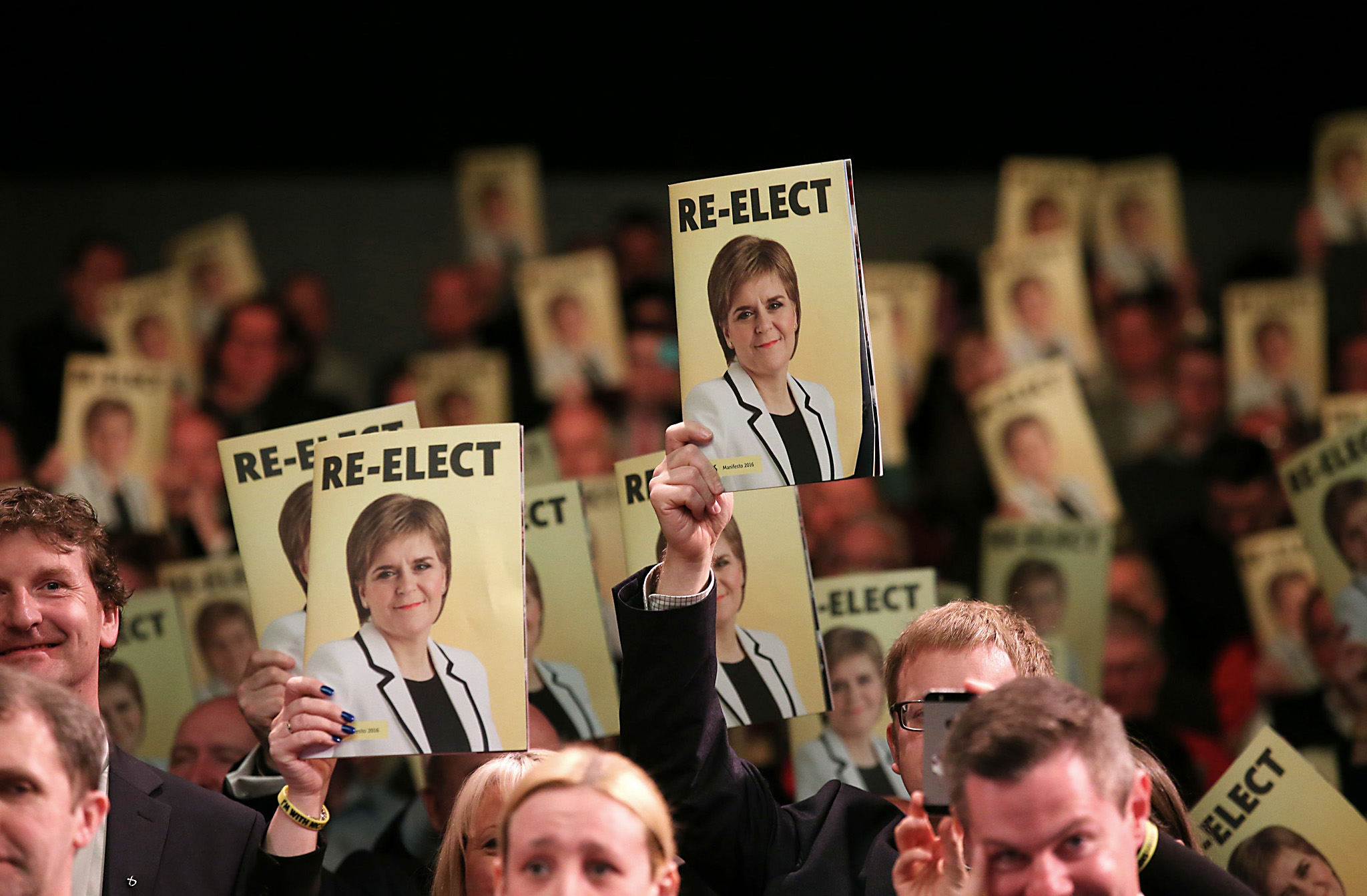 "Scottish Parliament election 2016 campaign ...Audience members hold the SNP party Scottish Parliament election manifesto up during its launch at the Edinburgh International Conference Centre in Edinburgh, as the party bids for its third term in power. PRESS ASSOCIATION Photo. Picture date: Wednesday April 20, 2016. The manifesto pledged to increase NHS funding by £500 million more than inflation over the five-year course of the next parliament, with Ms Sturgeon describing this as ""part of a package of investment and reform to equip the NHS for the future"". See PA story POLITICS SNP. Photo credit should read: Andrew Milligan/PA Wire"