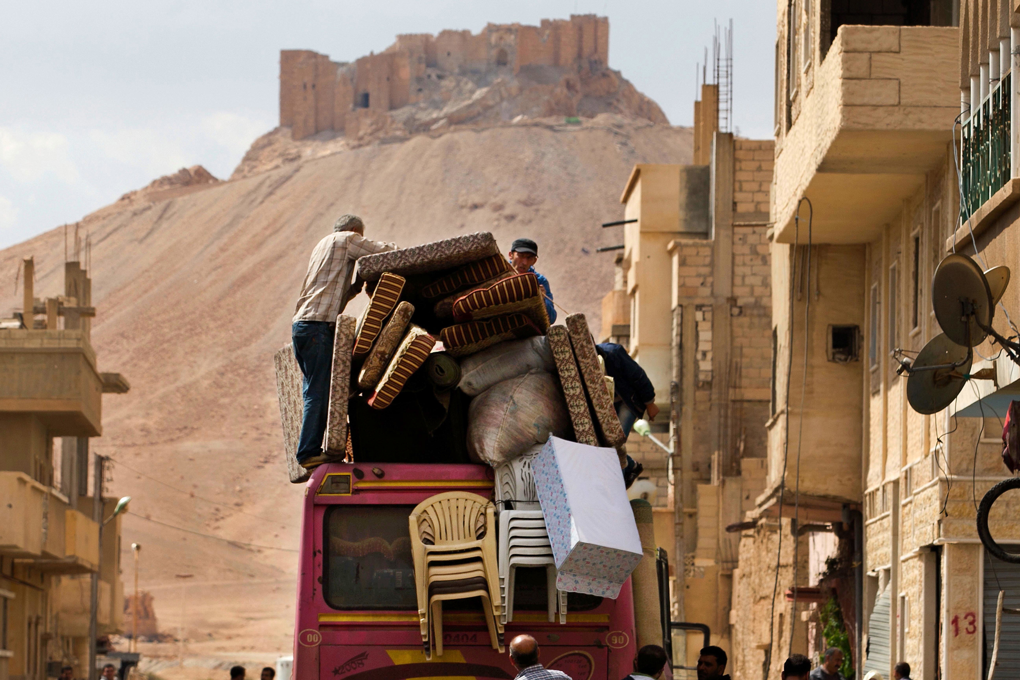 In this picture taken Thursday, April 14, 2016, the Palmyra citadel is seen in the background as Syrian families load their belongings onto a bus in the town of Palmyra in the central Homs province, Syria. Thousands of residents of this ancient town who fled Islamic State rule are returning briefly to check on their homes and salvage what they can _ some carpets, blankets, a fridge or a few family mementos. (AP Photo/Hassan Ammar)