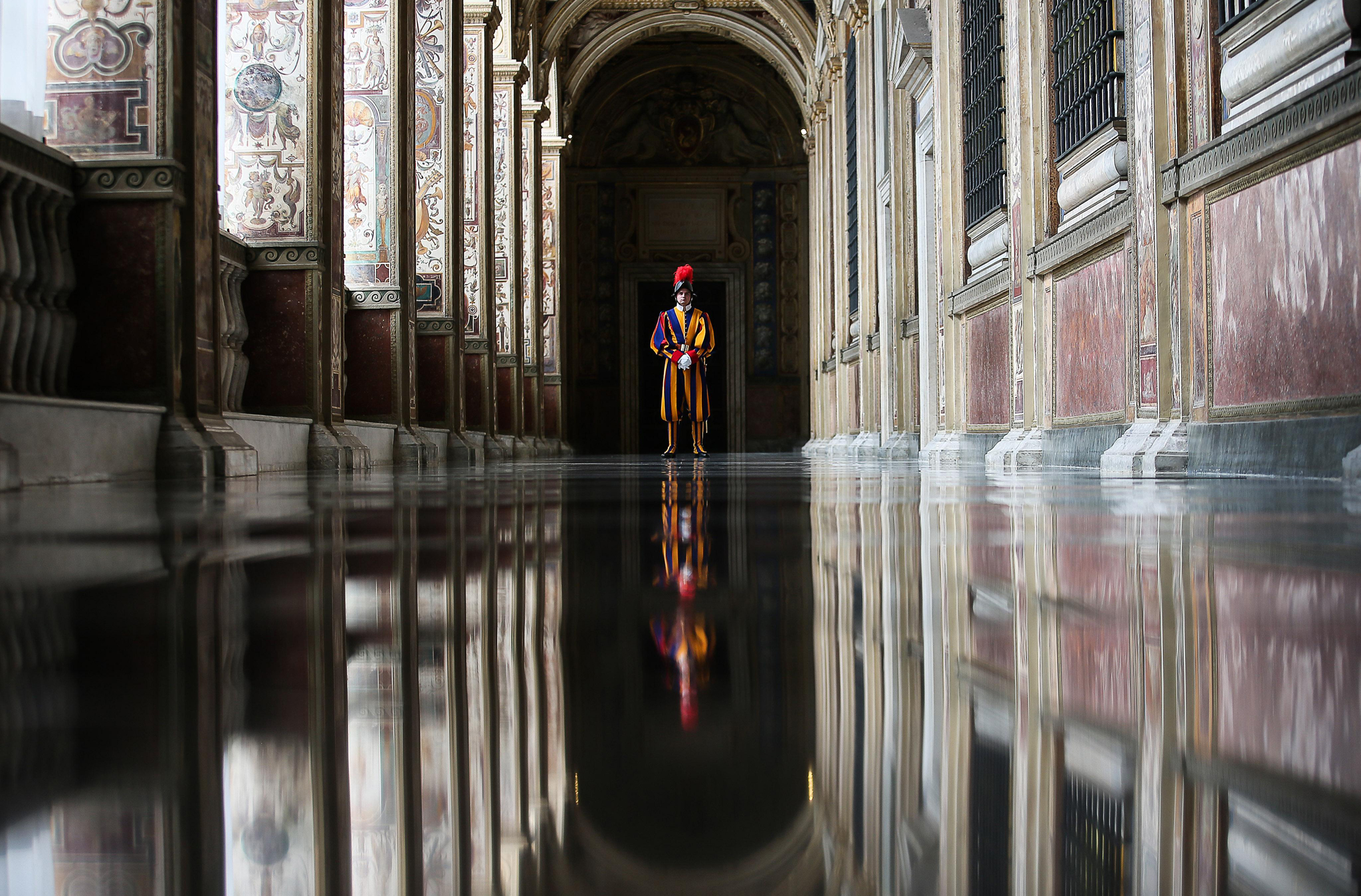 A Vatican Swiss guard stands in the corridor of the entrance of the Bronze Door of the Apostolic Palace, at the Vatican, Thursday, April 7, 2016. The door is the main entrance to the Palace and tradition goes that when a pontiff dies the door is closed by a Swiss guard. (Alessandro Di Meo/Pool Photo via AP)