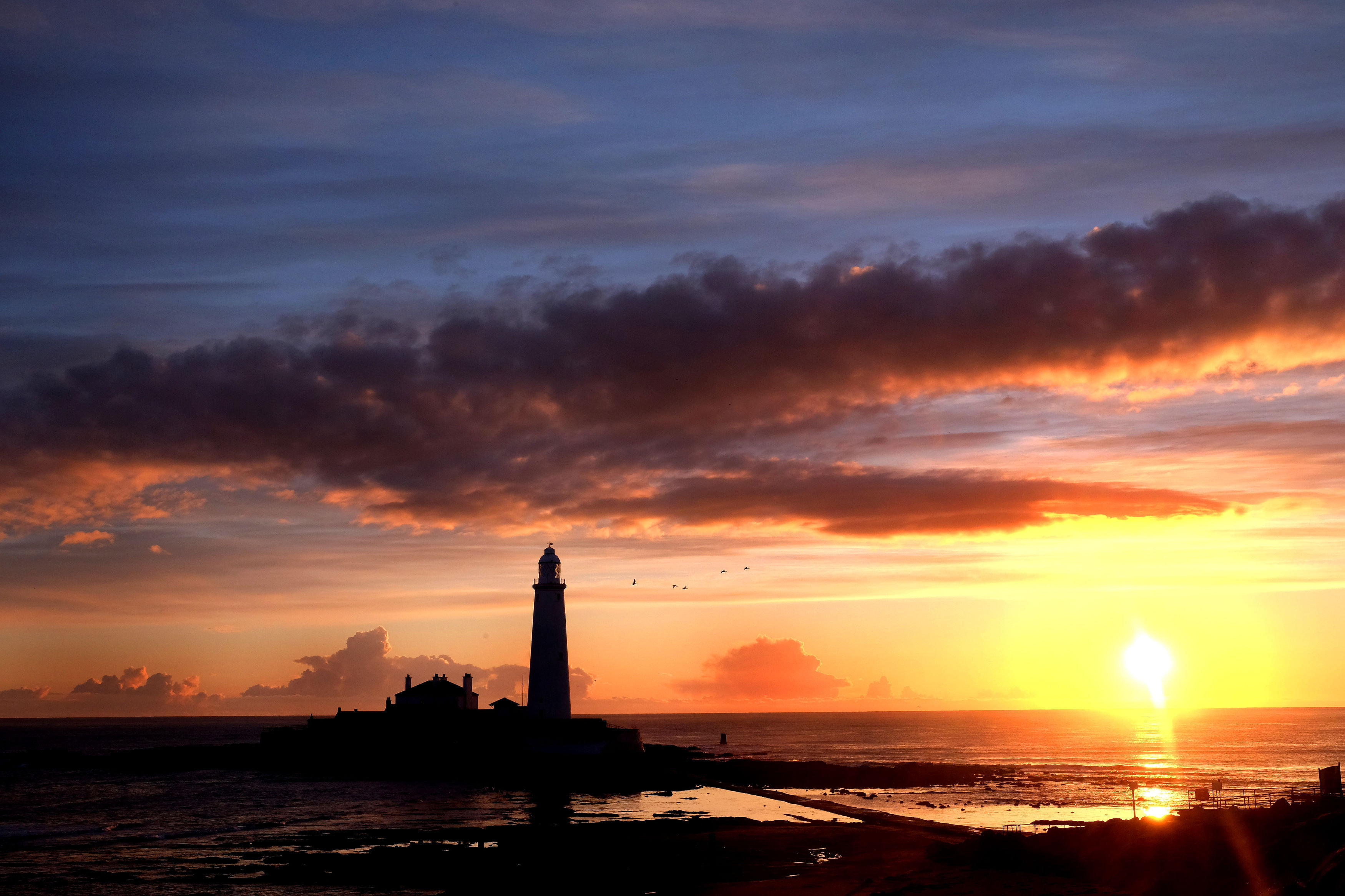 The sun rises beside St Mary's Lighthouse  in Whitley Bay