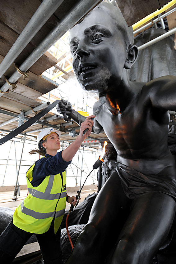 Wellington Arch sculpture conservation...Freelance sculpture conservator Scarlett Hutchin, working for English Heritage, buffs wax polish applied to  artist Adrian Jones' sculpture, Quadriga, on top of Wellington Arch at Hyde Park Corner, depicting four horses, representing the forces of chaos and war pulling a chariot, being calmed by the angel of peace, as the landmark sculpture is being cleaned, repaired and re-waxed by a team of specialists as part of a major English Heritage conservation programme. PRESS ASSOCIATION Photo. Picture date: Thursday April 7, 2016. See PA story HERITAGE Quadriga. Photo credit should read: Nick Ansell/PA Wire