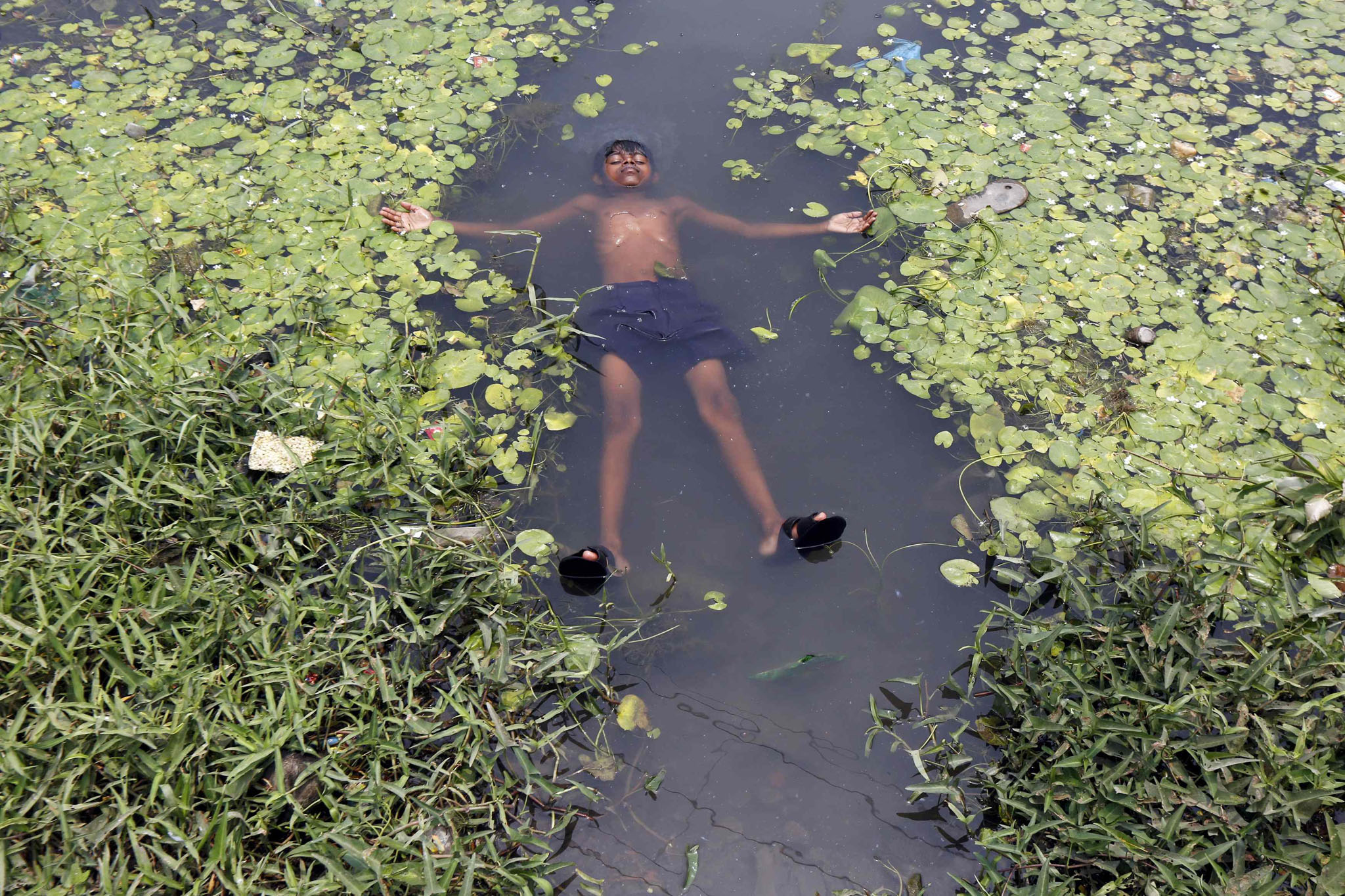 A boy floats in a pond to cool off on a hot summer day on the outskirts of Kolkata