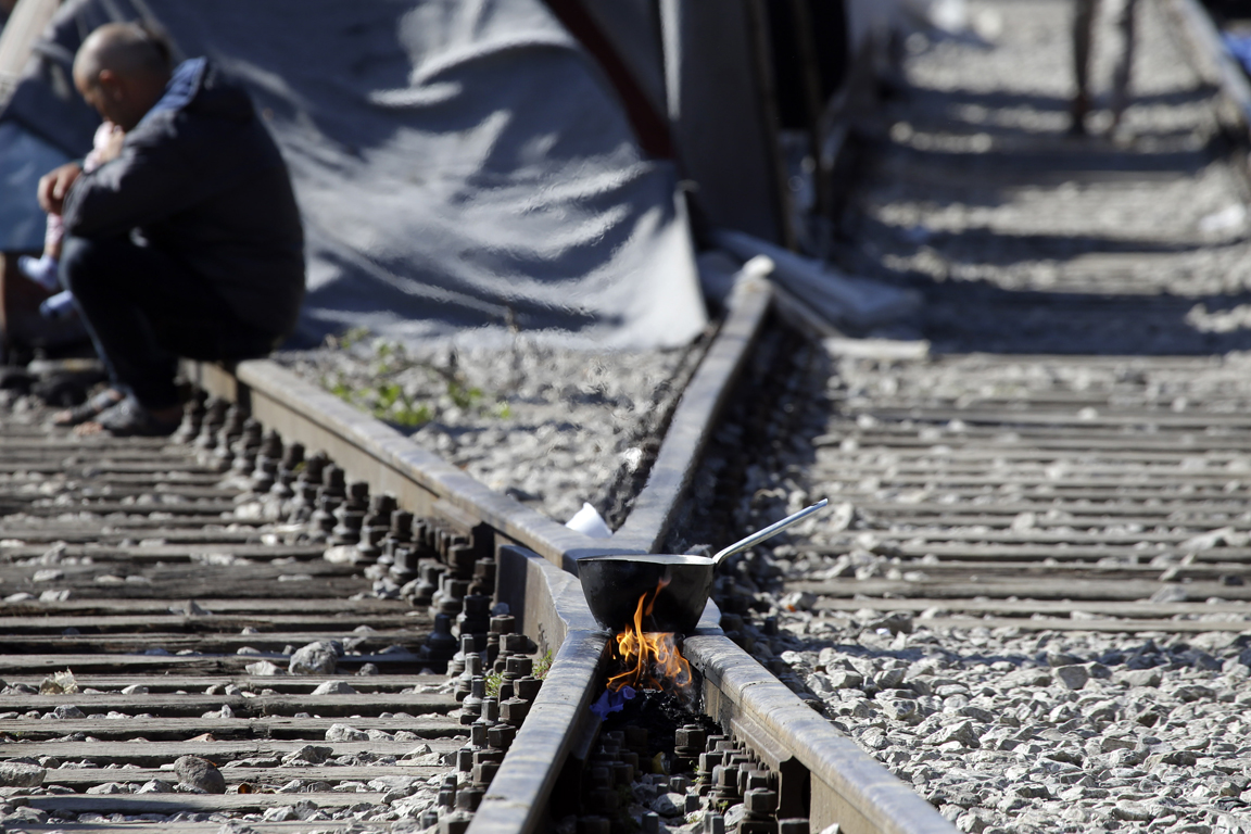 A pot over a bonfire was placed on the tracks of a railway station turned into a makeshift camp, crowded by migrants and refugees at the northern Greek border point of Idomeni, Greece, Monday, April 25, 2016. Many thousands of migrants remain at the Greek border with Macedonia, hoping that the border crossing will reopen, allowing them to move north into central Europe. (AP Photo/Gregorio Borgia)