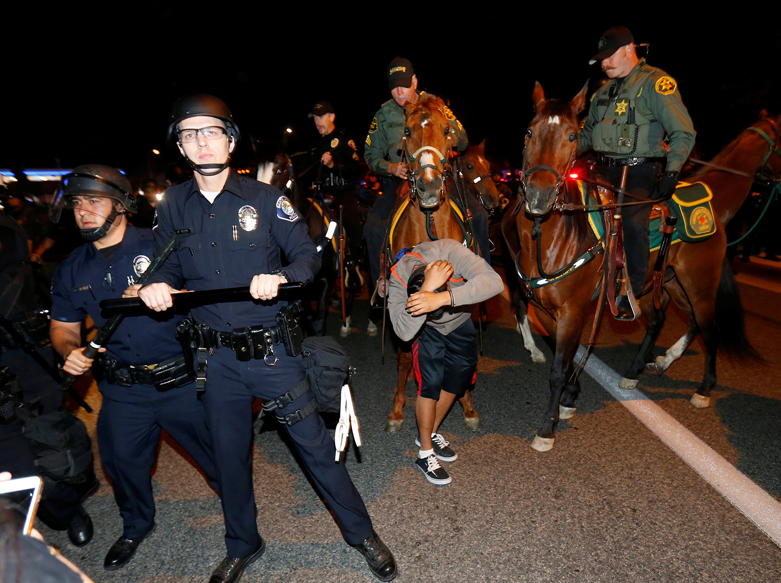 Sheriffs on horseback and police break up a group of demonstrators outside Republican U.S. presidential candidate Donald Trump's campaign rally in Costa Mesa