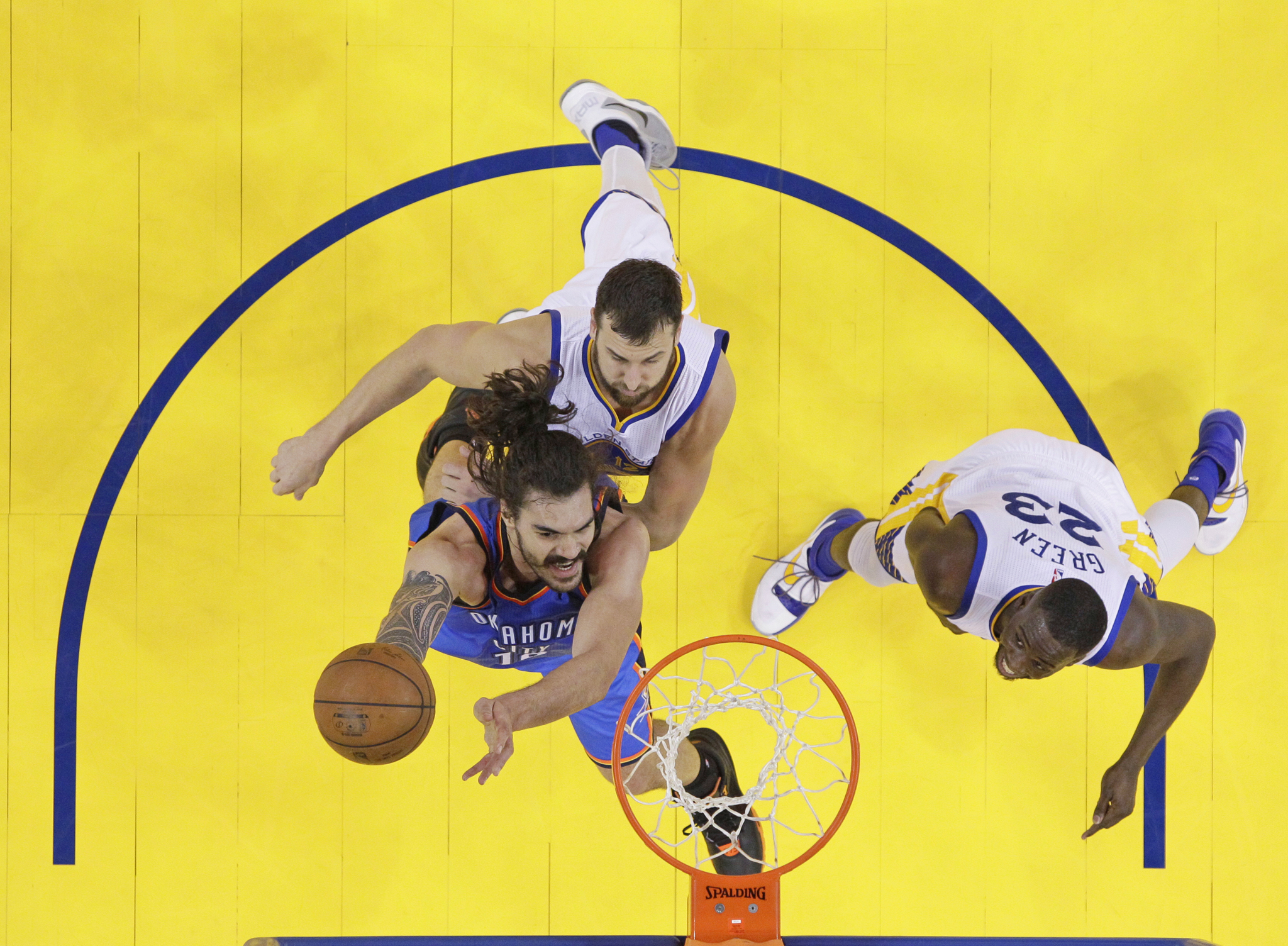 Oklahoma City Thunder's Steven Adams, bottom left, drives past Golden State Warriors' Andrew Bogut, top left, and Draymond Green (23) during the first half in Game 1 of the NBA basketball Western Conference finals Monday, May 16, 2016, in Oakland, Calif. Oklahoma City won 108-102