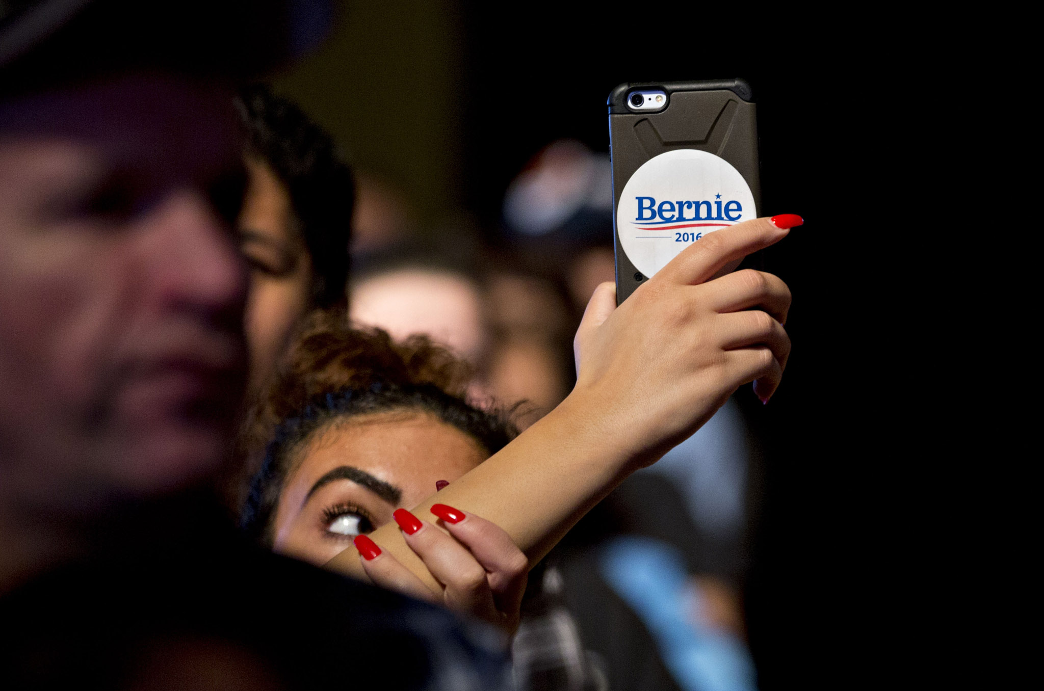 Presidential Candidate Bernie Sanders Holds Atlantic City Campaign Rally...An attendee with a campaign sticker on her phone takes video as Senator Bernie Sanders, an independent from Vermont and 2016 Democratic presidential candidate, not pictured, speaks during a rally at Boardwalk Hall in Atlantic City, New Jersey, U.S., on Monday, May 9, 2016. Atlantic City, the struggling casino hub weeks away from bankruptcy absent state action that has been hit hard by the decline of its dominant industry, is a fitting platform for Sanders populist message on how corporations reap profits while urban areas are neglected. Photographer: Andrew Harrer/Bloomberg