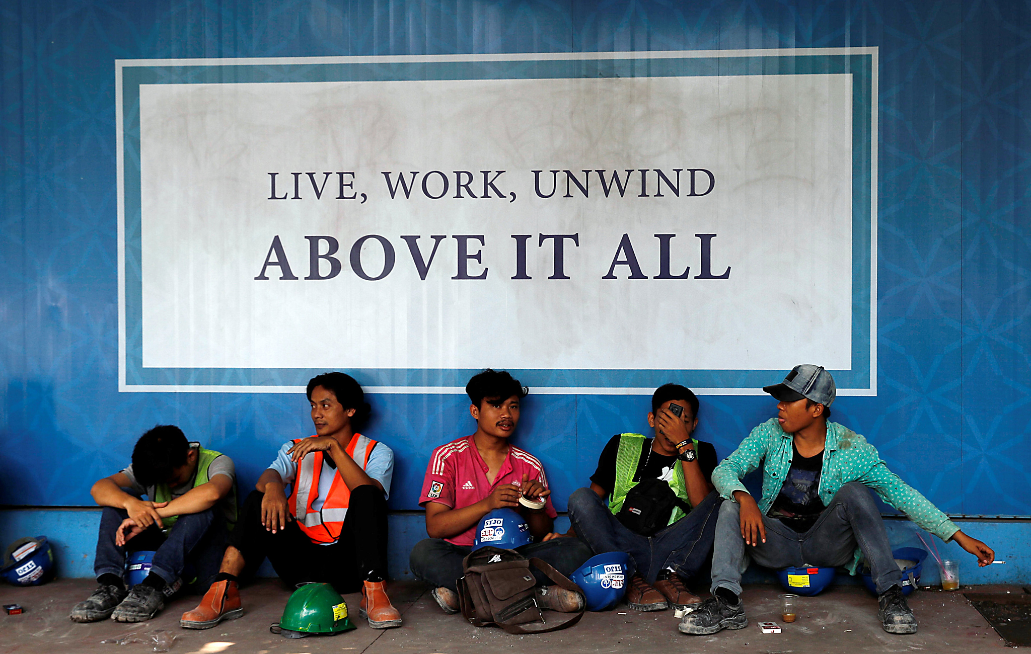 Workers sit as they take a break near a banner of a new apartment in Jakarta, Indonesia, May 18, 2016. REUTERS/Beawiharta
