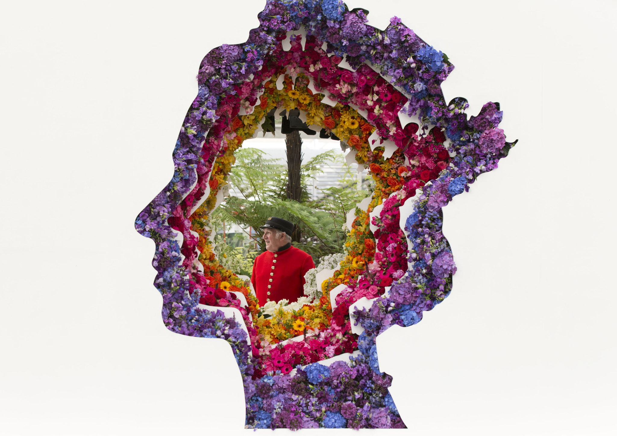 A Chelsea Pensioner is seen through New Covent Garden Flower Market's tribute to Queen Elizabeth II - a three metre high profile of the Queen made from over 5,000 cut flowers, during a press day ahead of the Chelsea Flower Show at the Royal Hospital Chelsea in London. PRESS ASSOCIATION Photo. Picture date: Monday May 23, 2016. See PA story CONSUMER Chelsea. Photo credit should read: Yui Mok/PA Wire