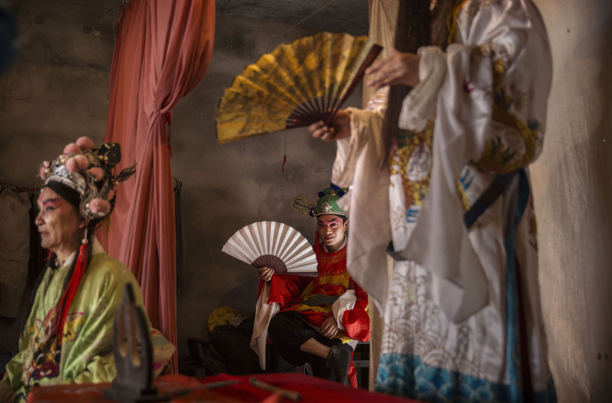 Keeping The Tradition Of Opera Alive In Rural China...CANGSHAN, SICHUAN - MAY 02:  Sichuan Opera actors from the Jinyuan Opera Company perform for villagers at the Dongyue Temple on May 2, 2016 in Cangshan, Sichuan province, China. Sichuan opera is a vibrant, centuries-old tradition that showcases the joys and challenges of daily life in rural China with tales of love, tradition, and family honor. As the traditional audience grows older, the opera as a form of art and recreation is struggling to endure as newer spectators within younger generations are leaving the countryside for China's cities to seek employment.  The tradition suffered a setback 50 years ago during the Cultural Revolution, the period of persecution and upheaval set into motion in May 1966 by Communist Party Chairman Mao Zedong to reassert his ideological authority. The operas were banned and most of the troupes were disbanded, but were revived in the late 1970s. (Photo by Kevin Frayer/Getty Images)