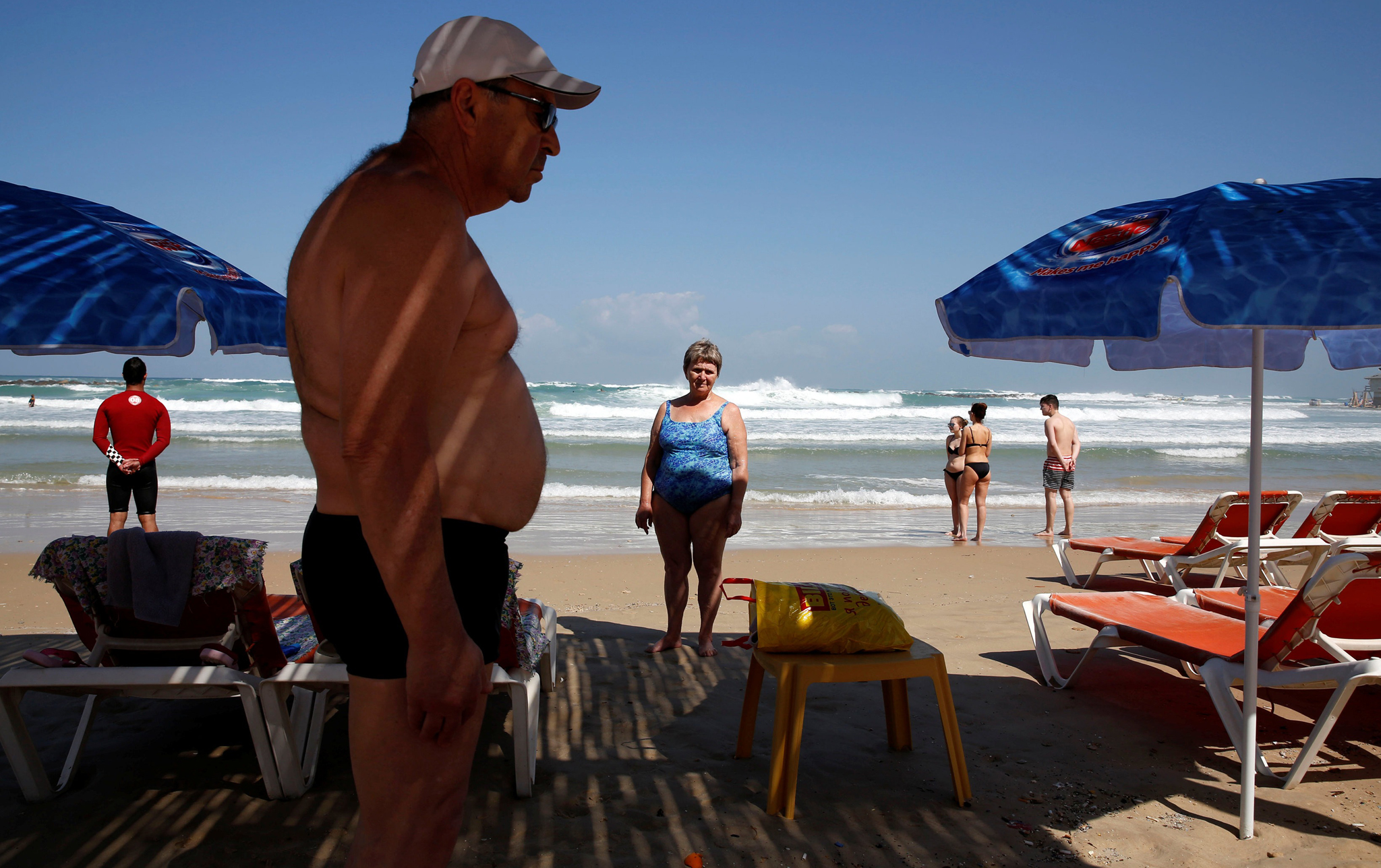 Beach-goers stand still as a two-minute siren marking annual Holocaust Remembrance Day in Israel is sounded in Netanya, Israel May 5, 2016