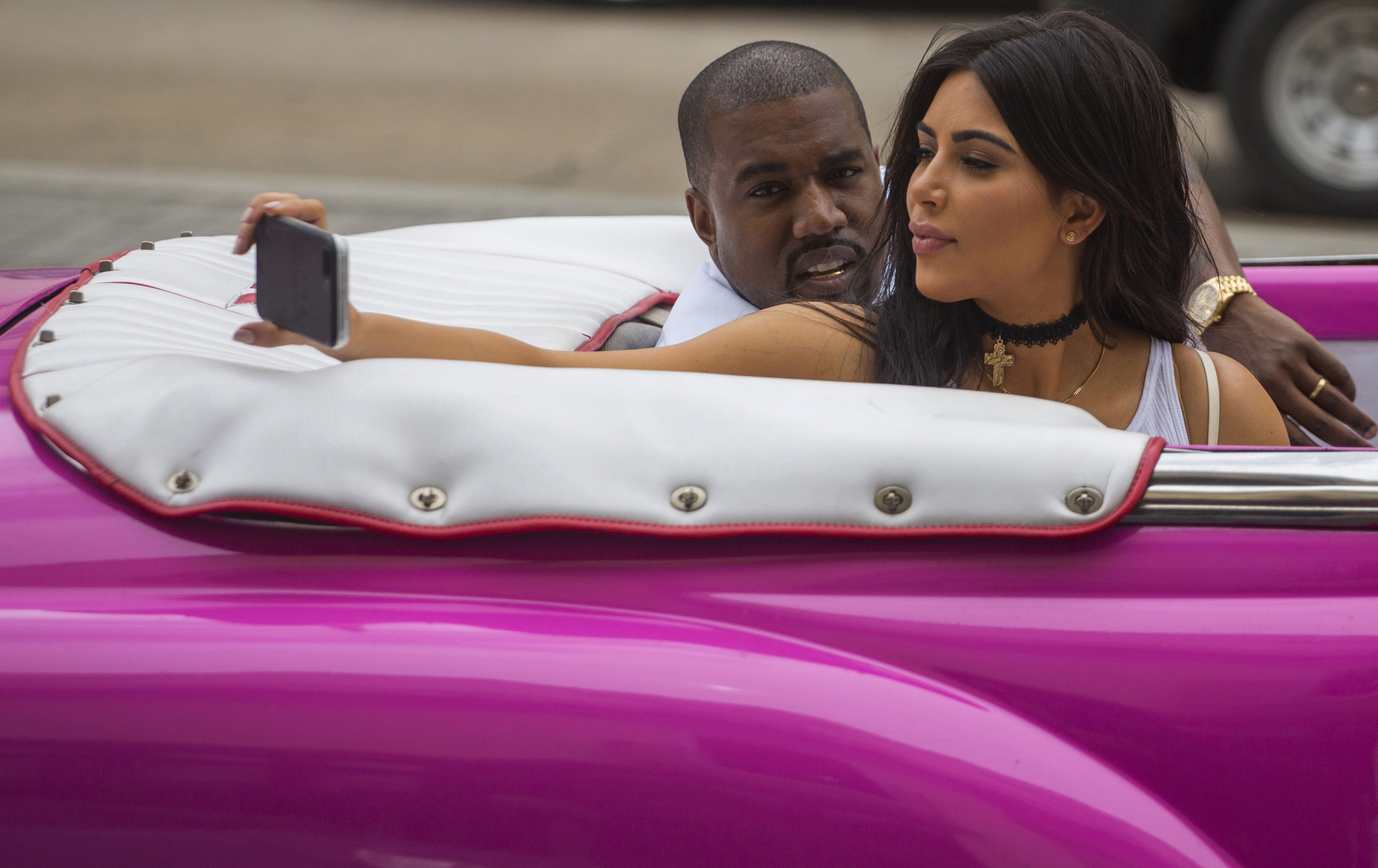 American reality-show star Kim Kardashian takes a selfie as she rides on a classic car next to her husband, rap superstar Kayne West in Havana, Cuba, Wednesday, May 4, 2016