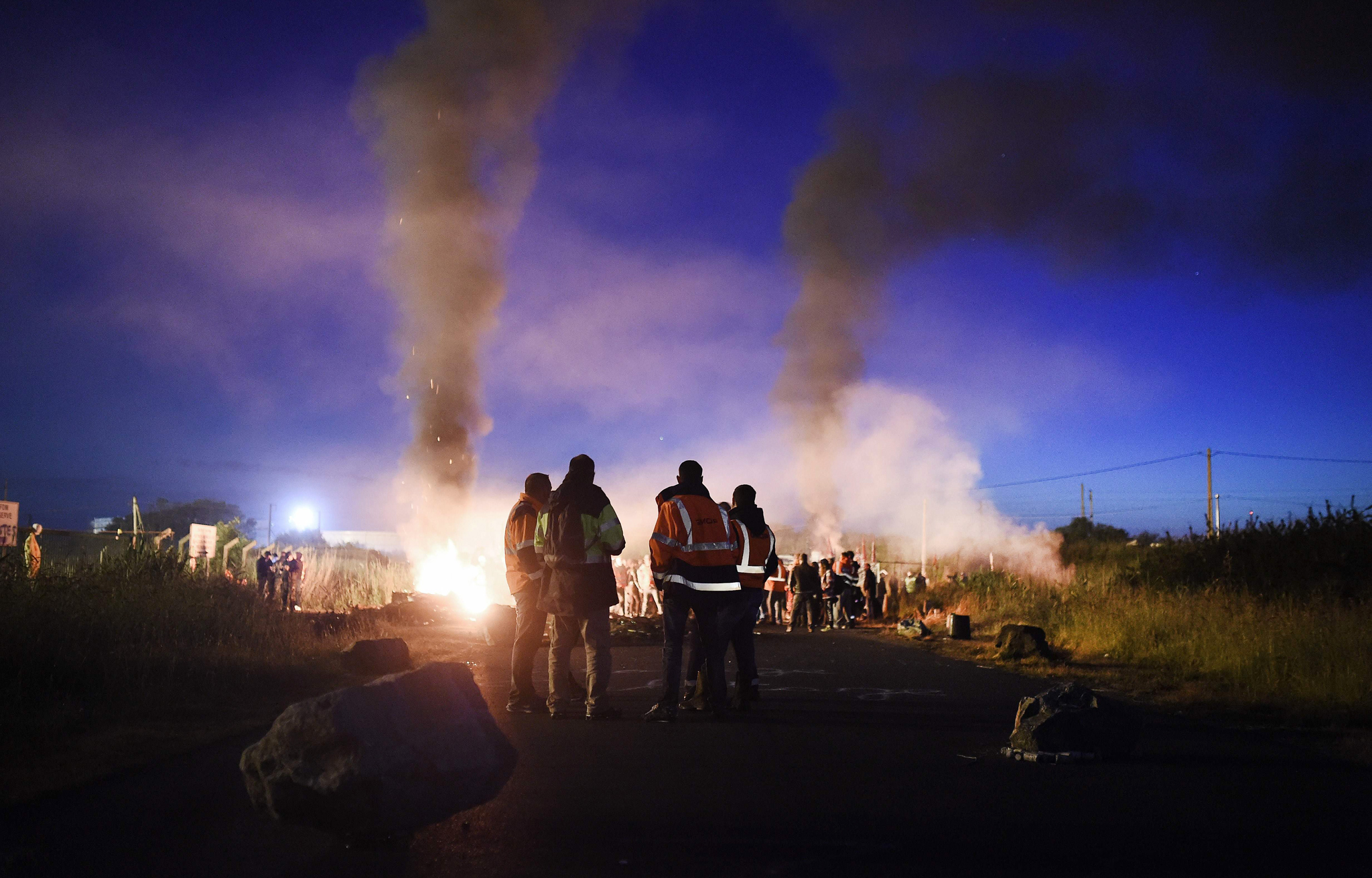 TOPSHOT - Men stand next to a fire as wo...TOPSHOT - Men stand next to a fire as workers on strike block the access to an oil depot near the Total refinery of Donges, western france, early in the morning on May 27, 2016 to protest against the government's planned labour law reforms.