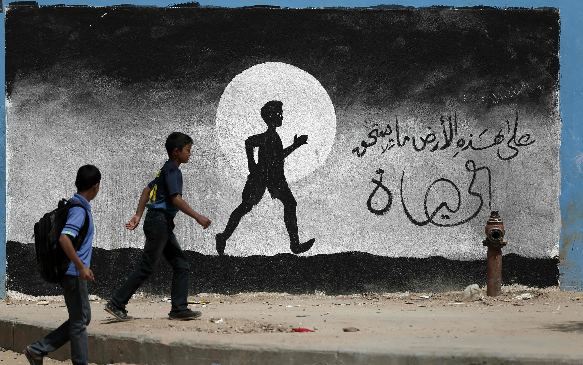 Two Palestinian schoolboys walk past a g...Two Palestinian schoolboys walk past a graffiti painted on a wall of the United Nations school of Beit Hanun, in the northern Gaza Strip, on May 9, 2016.  / AFP PHOTO / THOMAS COEXTHOMAS COEX/AFP/Getty Images