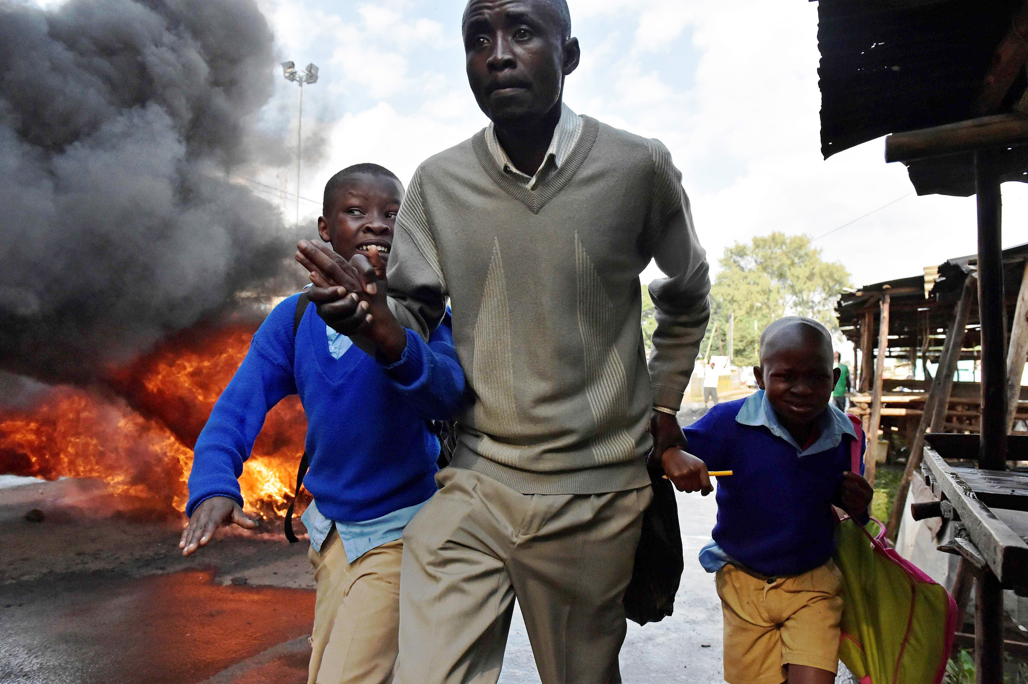TOPSHOT - A man leads school children away from teargas and a burning barricade in Kibera slum, Nairobi on May 23, 2016 during a demonstration of opposition supporters demanding a change of leadership at the electoral commission ahead of a vote due next year.  Local media reported at least one killed in Kisumu in the west of the country, while police in Nairobi and the second city of Mombasa fought running battles with small groups of protesters. There was no immediate police confirmation of the reported death. Police had banned the planned demonstrations and scores of officers in riot gear guarded the building that houses the election commission headquarters in the centre of the capital.  / AFP PHOTO / CARL DE SOUZACARL DE SOUZA/AFP/Getty Images