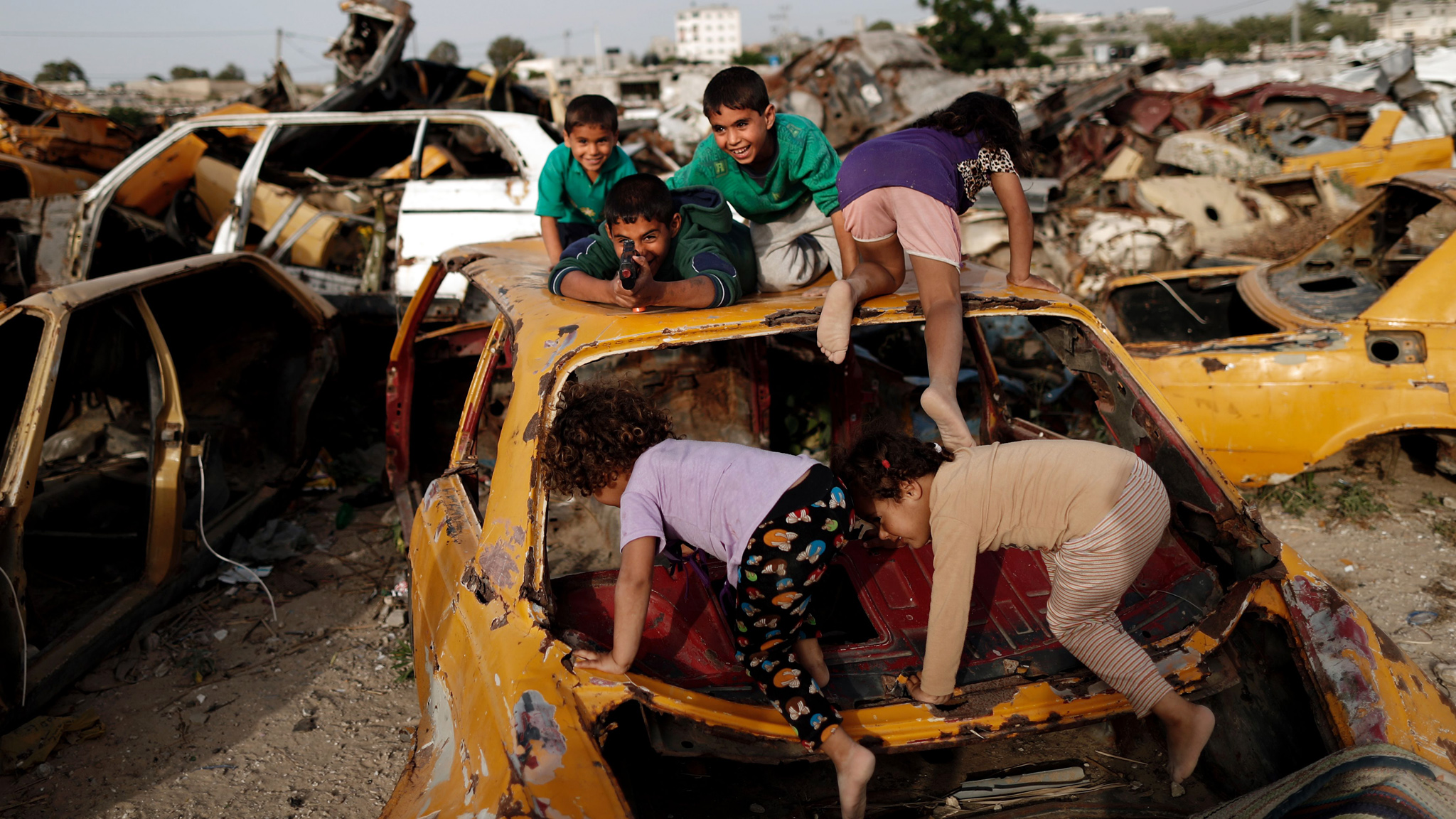 TOPSHOT - Palestinian children play amid...TOPSHOT - Palestinian children play amidst wrecked cars in an impoverished area in the southern Gaza Strip city of Khan Yunis, on May 9, 2016.  / AFP PHOTO / THOMAS COEXTHOMAS COEX/AFP/Getty Images