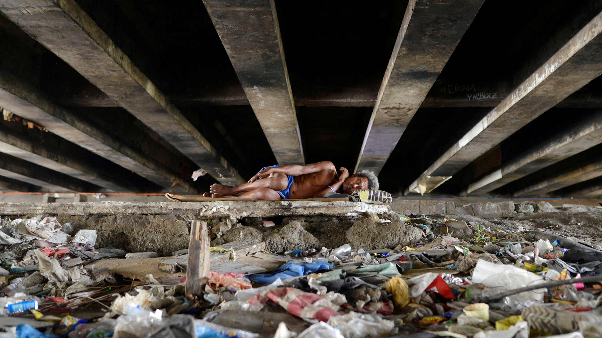 A man sleeps amidst rubbish under a bridge in Paranaque city, Metro Manila...A man sleeps amidst rubbish under a bridge in Paranaque city, Metro Manila, Philippines May 31, 2016. REUTERS/Ezra Acayan