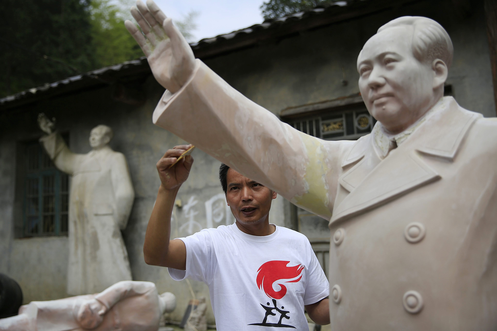 epa05300699 A picture made available on 12 May 2016 shows Chinese sculptor Tian Yongjun working on a Mao Zedong sculpture outside his workshop in Shaoshan, Hunan Province in central China, 29 April 2016. Shaoshan is the hometown of former Communist leader Mao Zedong, popularly known as Chairman Mao. As the 50th anniversary of the Cultural Revolution approaches on 16 May, there is scant mention of the revolution where millions of intellectuals were persecuted and tortured in a bid to purge Mao's critics in his this small town where he was hailed as a great hero and leader.  EPA/HOW HWEE YOUNG