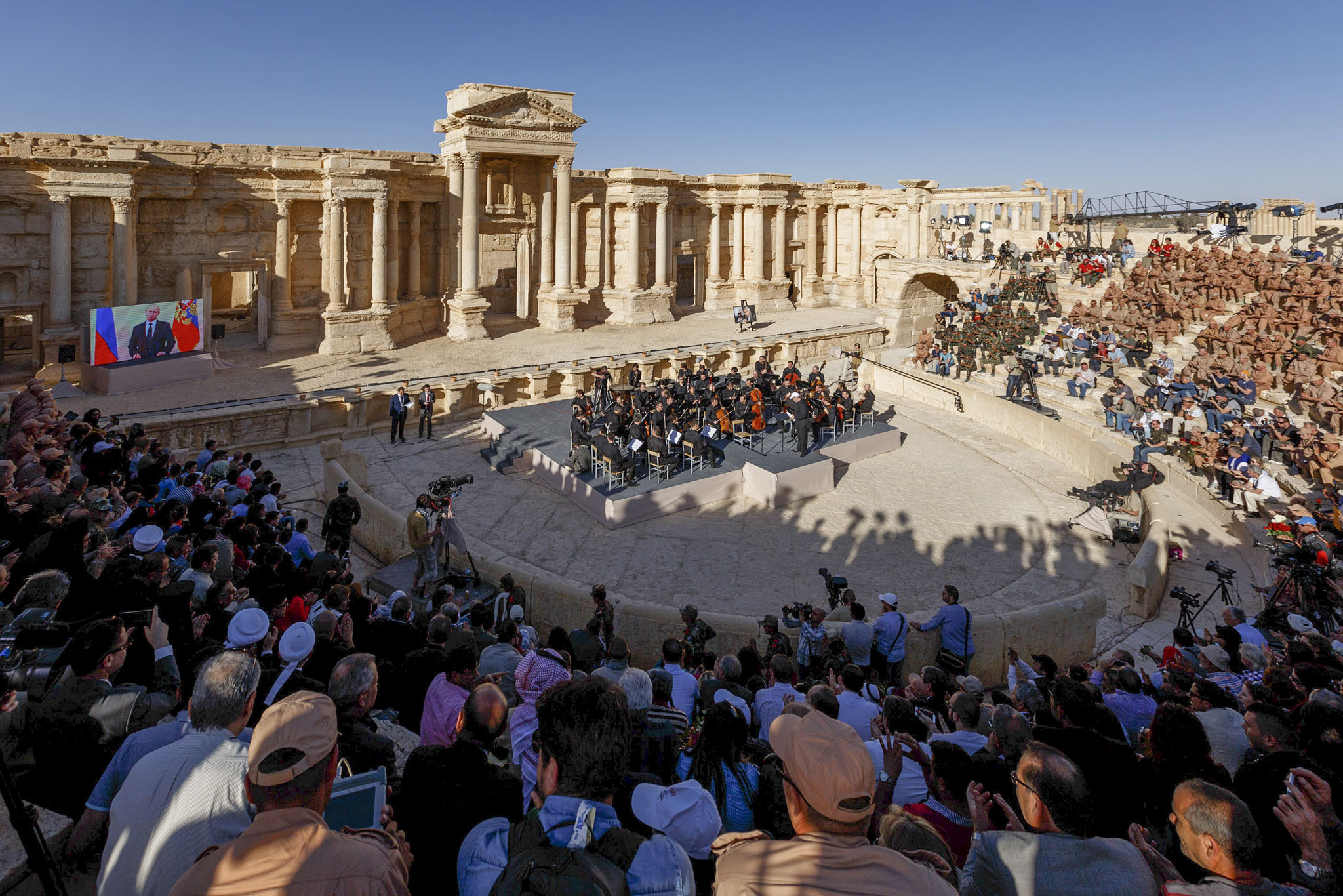 This Thursday, May 5, 2016 photo provided by Russian Defense Ministry Press Service, shows the concert at the UNESCO world heritage site of Palmyra, the central city of Homs, where renowned conductor Valery Gergiev leads a performance by the Mariinsky Symphony Orchestra from St. Petersburg, Syria. The renowned Russian conductor led a triumphant concert Thursday in the ruins of the ancient Syrian city of Palmyra, once terrorized by the Islamic State group, even as an airstrike on a refugee camp in the north left dozens of people dead and dozens wounded, including many children. (Olga Balashova/Russian Defense Ministry Press Service via AP)