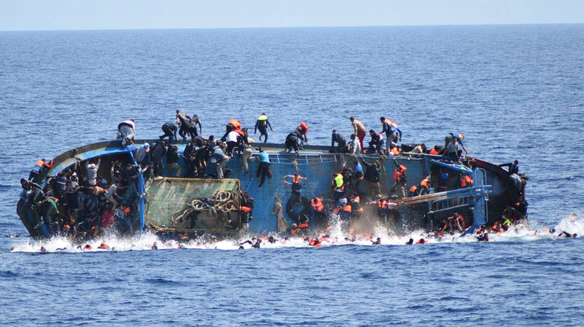 A handout picture released by the Italian Navy shows people jumping out of a boat right before it overturns in Canal of Sicily off the Libyan coast, 25 May 2016. The Italian navy says it has recovered five bodies from the overturned migrant ship.