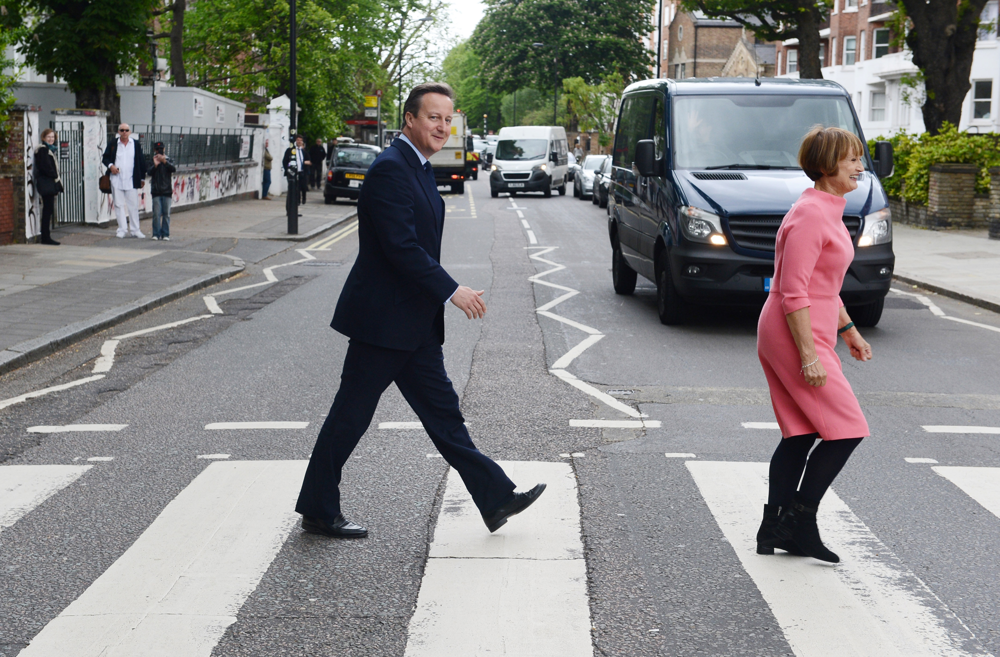 Prime Minister David Cameron recreates the famous Beatles Abbey Road album cover by walking across Abbey Road crossing with Tessa Jowell, former secretary of state for culture, media and sport, on May 20, 2016 in London, England