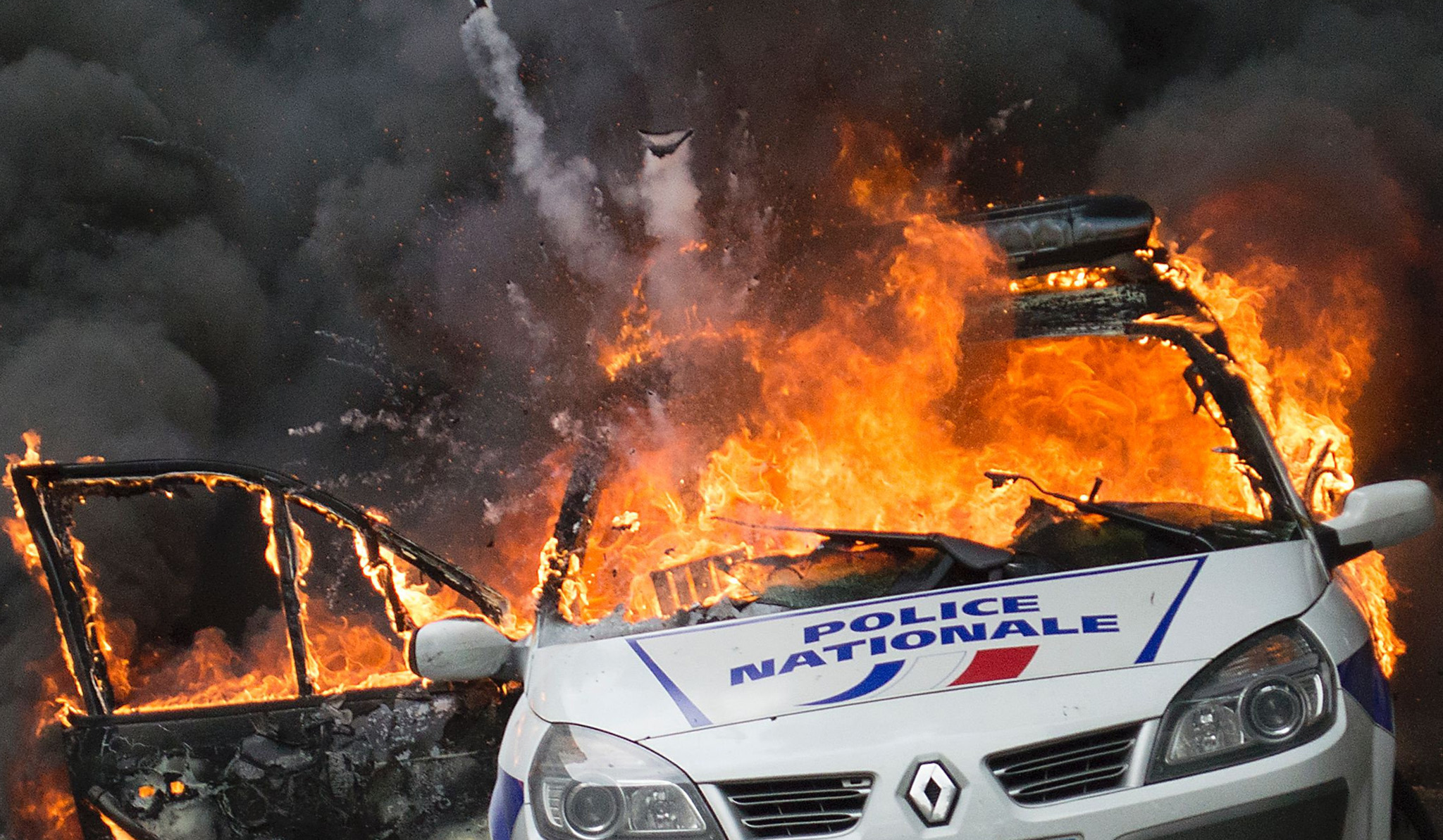 A police car explodes after being set on fire during an unauthorized counter-demonstration against police violence on May 18, 2016 in Paris